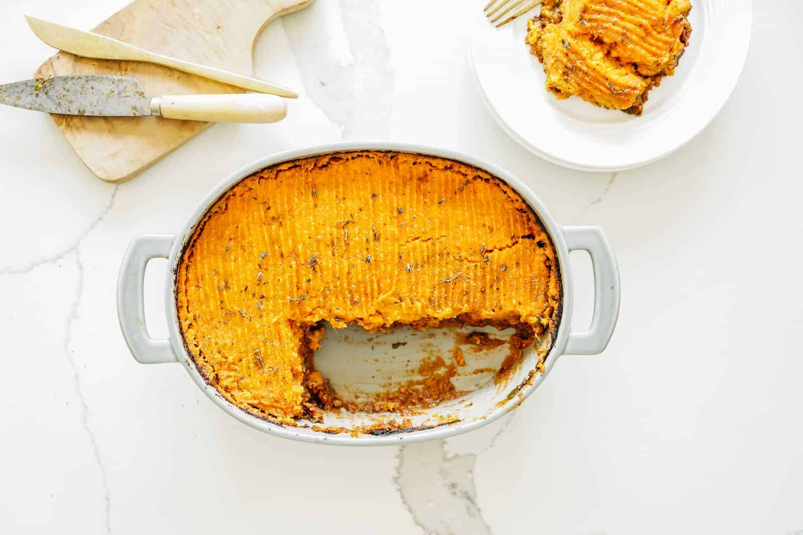 A casserole dish filled with Shepherd's Pie with a slice taken out of it.