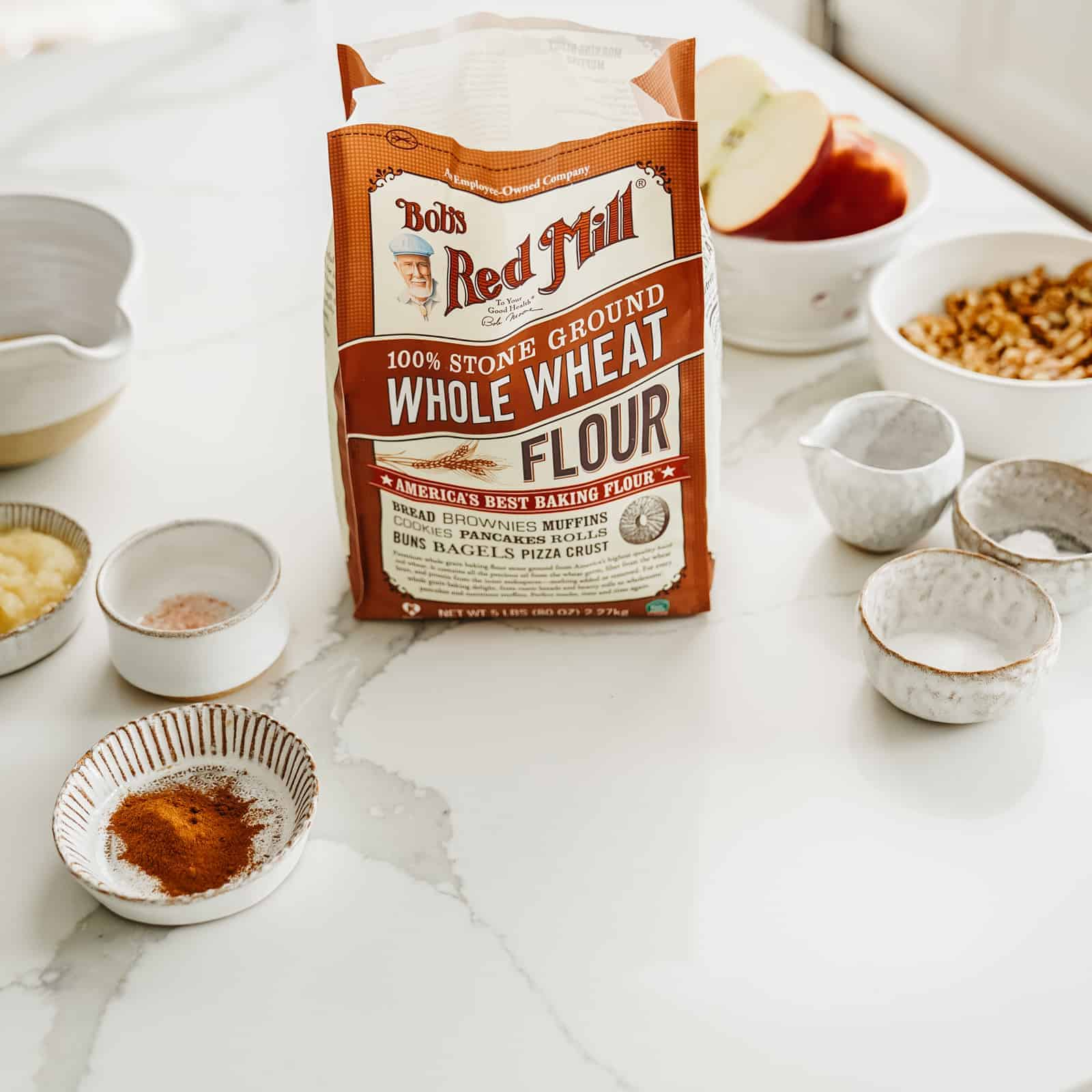 Bag of Bob's Red Mill Whole Wheat Flour sitting on countertop surrounded by other muffin ingredients.