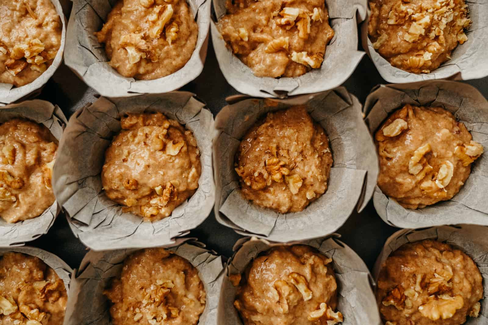 A dozen Vegan Apple Cinnamon Muffins all lined up in muffin wrappers on counter.