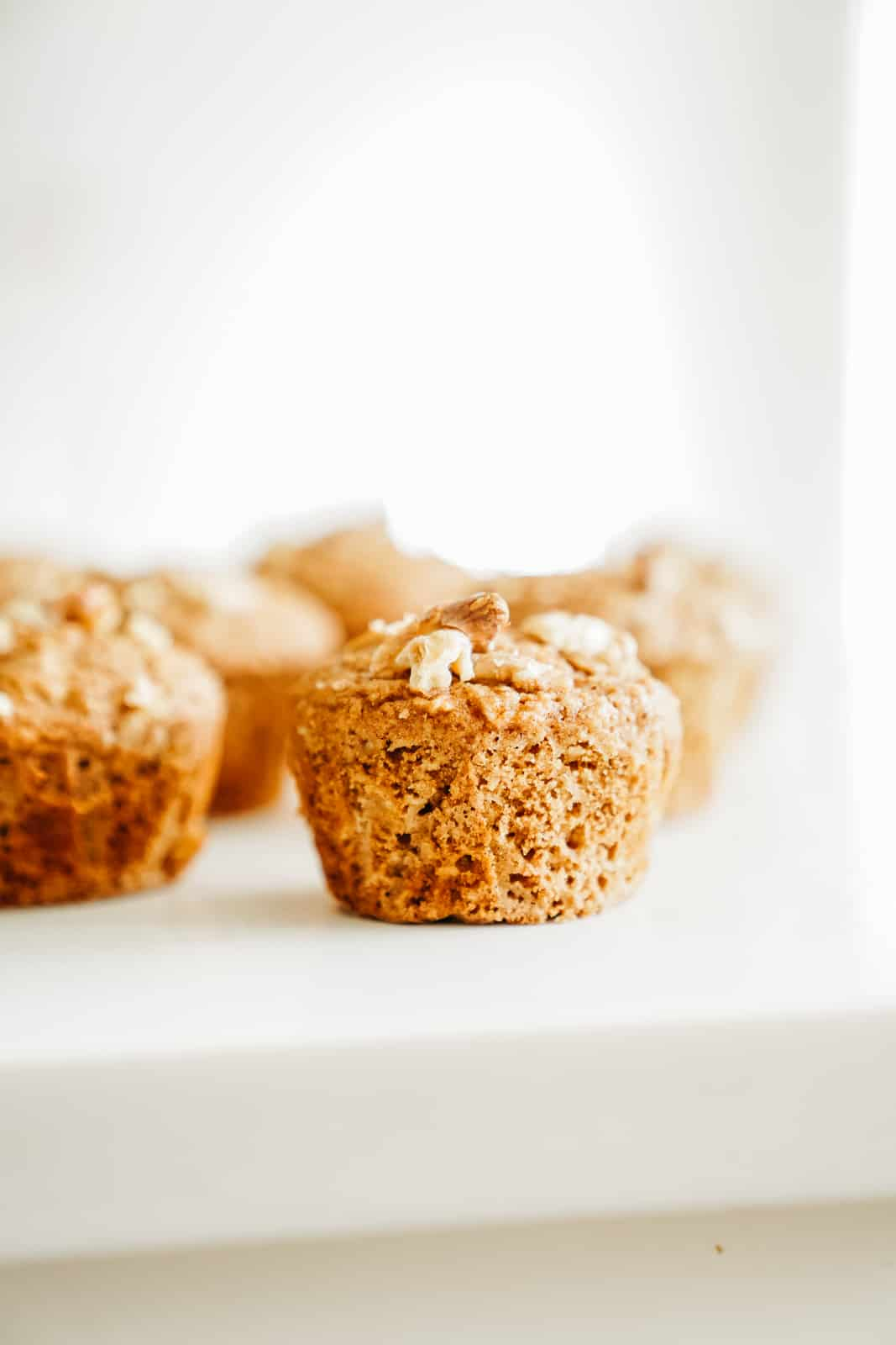 Close-up of Vegan Apple Cinnamon Muffins on a white countertop.