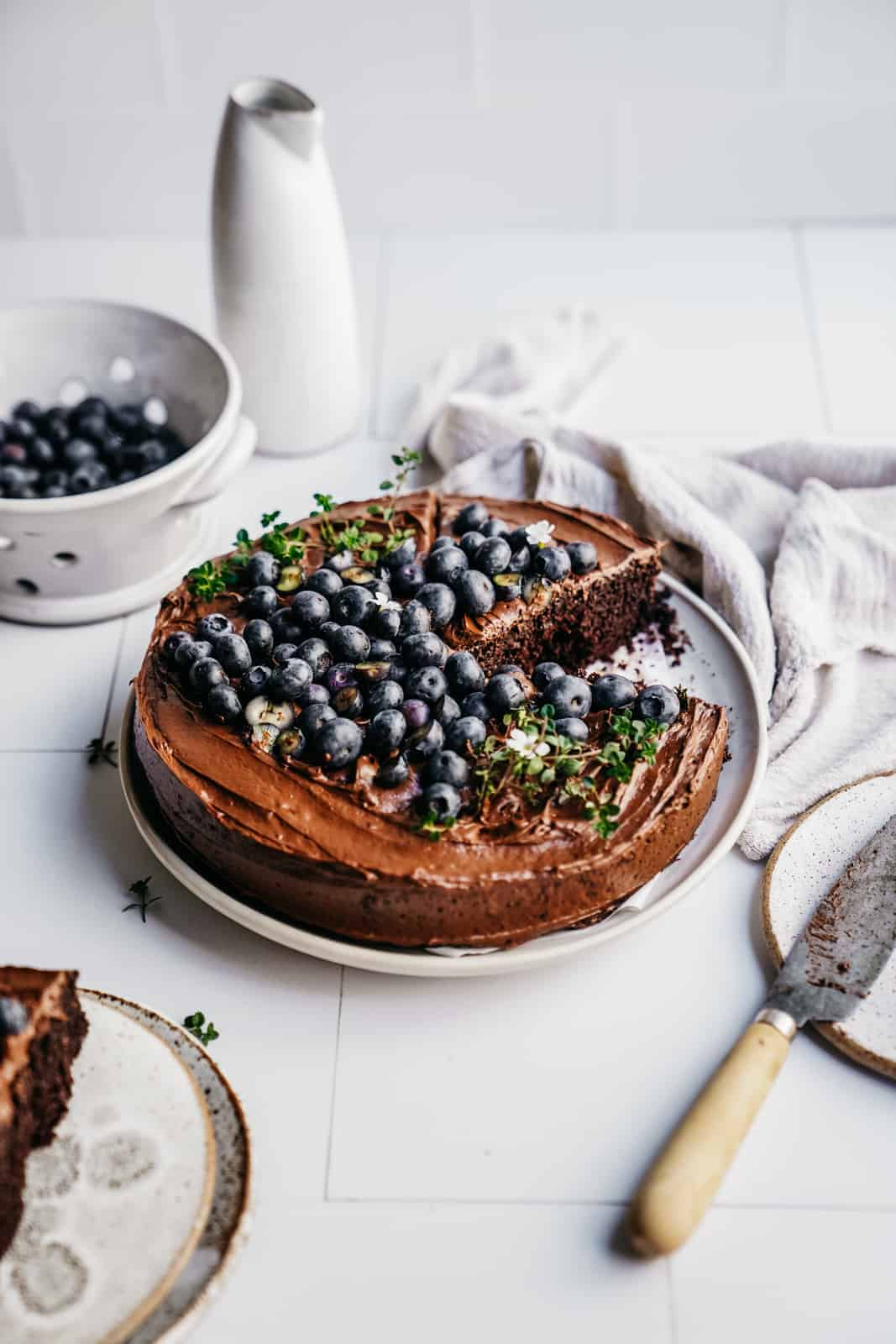 Easy Vegan Chocolate Cake on countertop with fresh blueberries on top.