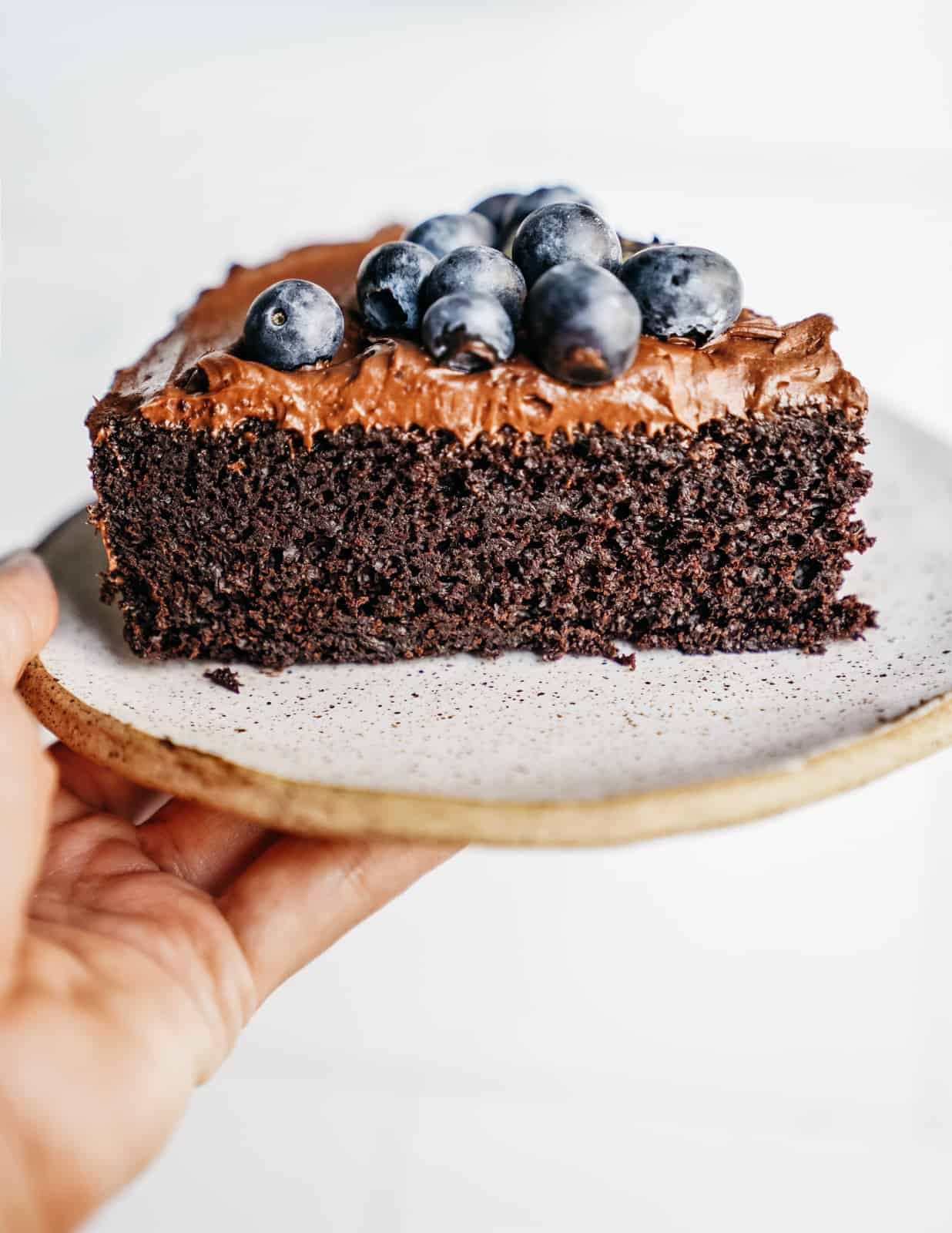 Close-up of a slice of moist Easy Vegan Chocolate Cake garnished with cashew frosting and blueberries.