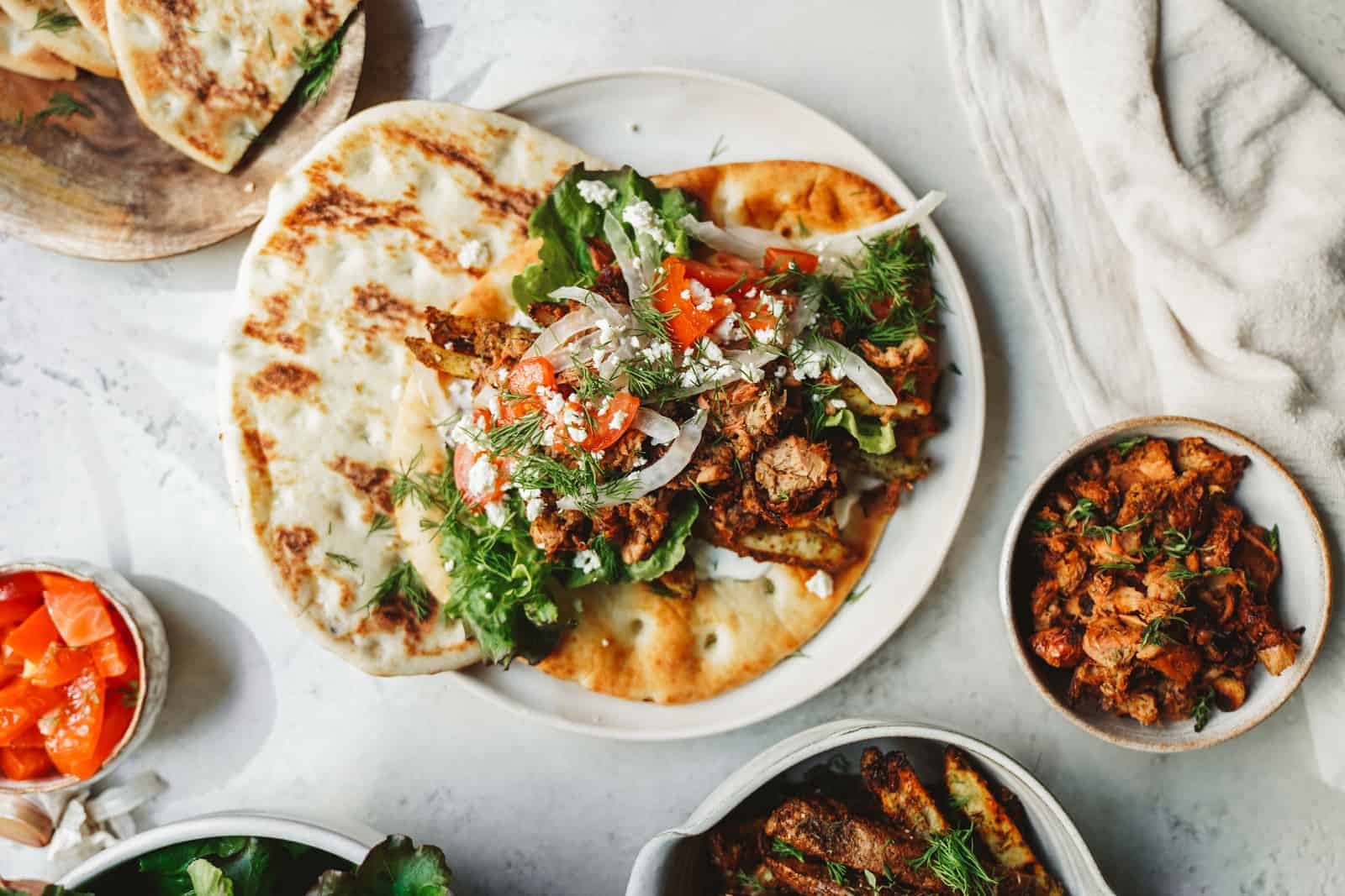 Yummy jackfruit gyros laid out on fresh pita with fresh herbs and tomato toppings. One of the best vegan meals.