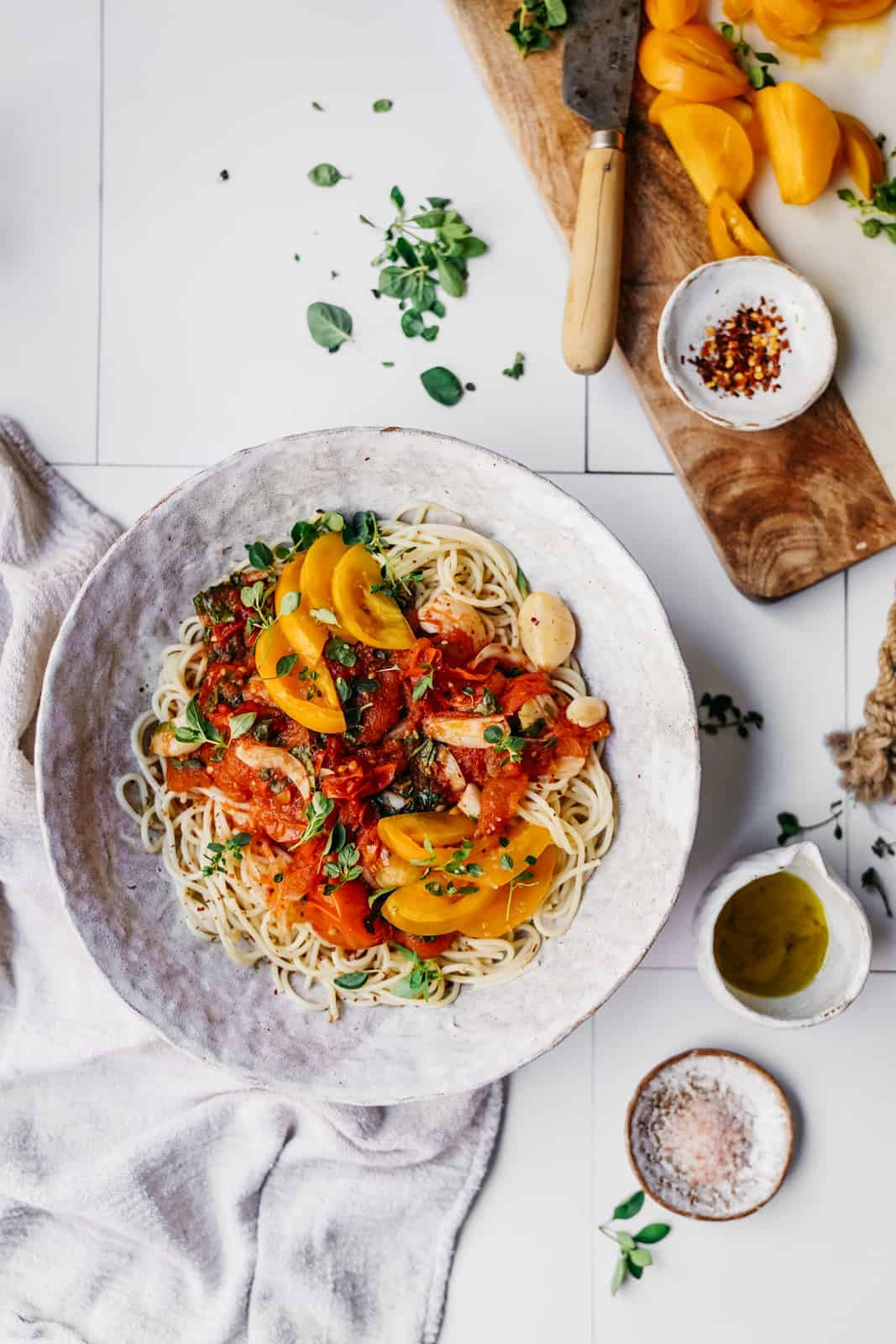 Big white bowl of Tomato and Garlic Pasta on a counter surrounded by little bowls of fresh ingredients.