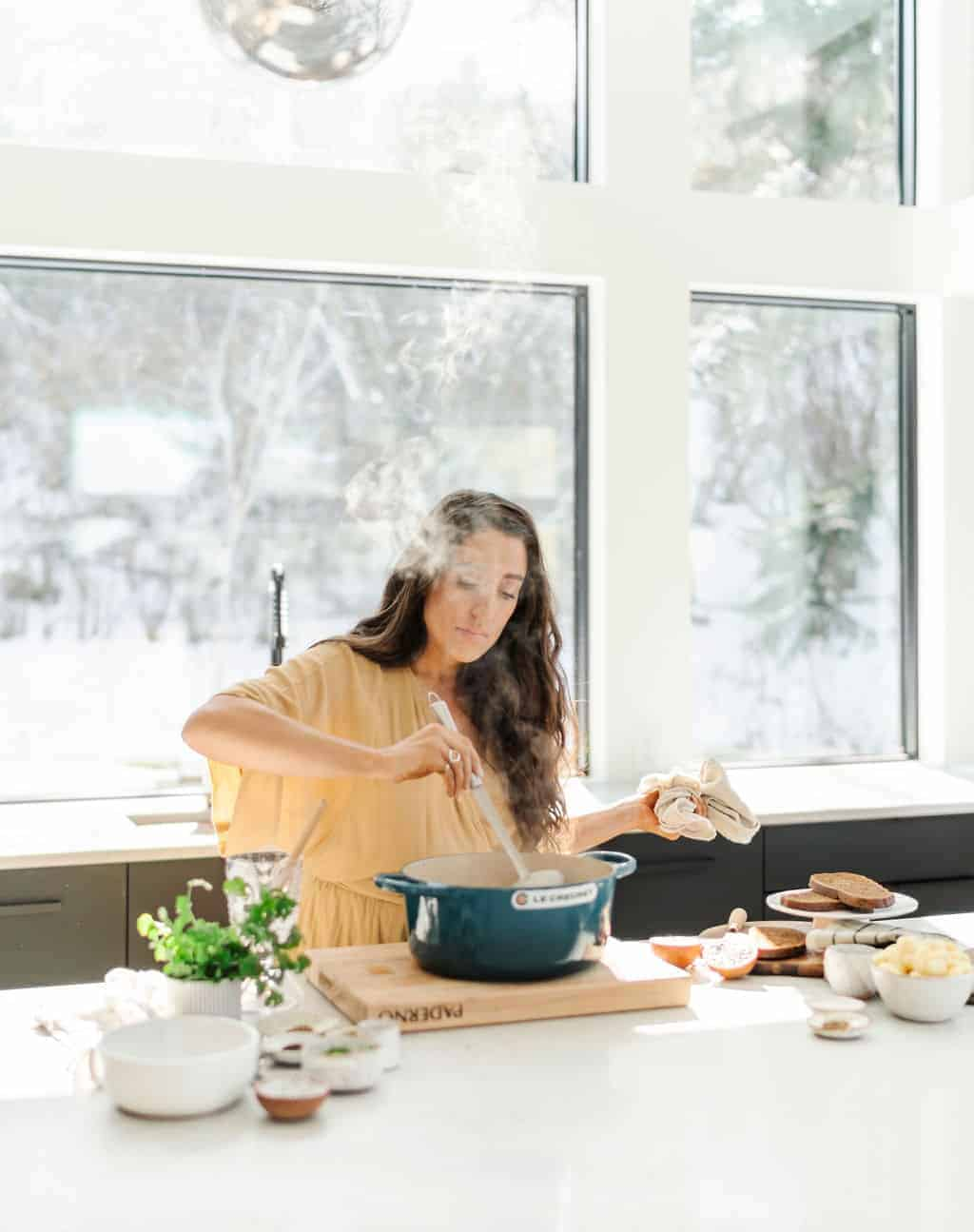 Maria stirring a pot of hot food at a white countertop with a beautiful winter backdrop