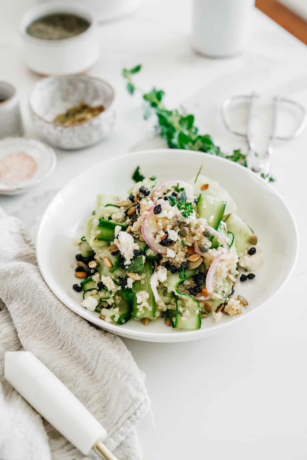 White bowl of Shaved Cucumber Salad with ingredients surrounding it.