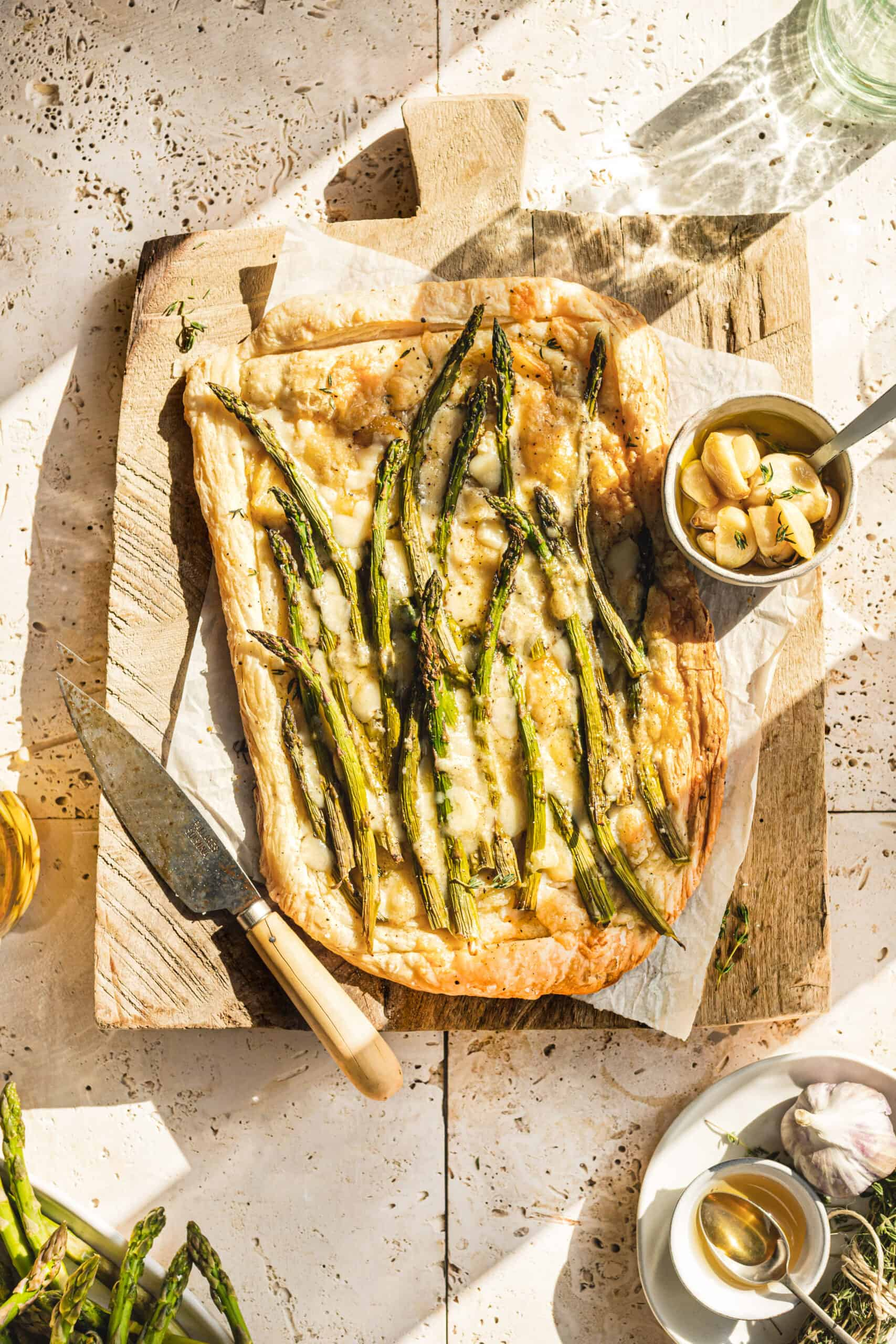 Asparagus and Cheese Tart on cutting board with sun shining through window.