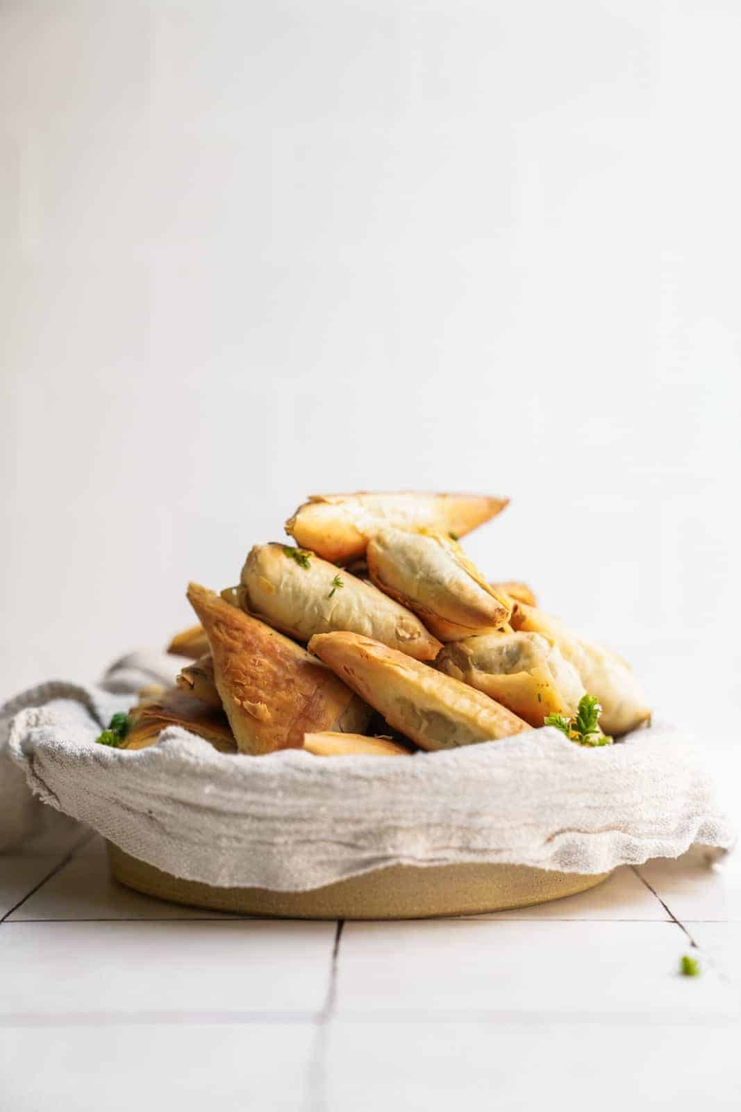 Serving dish of phyllo Creamy Mushroom Pastry bites on counter