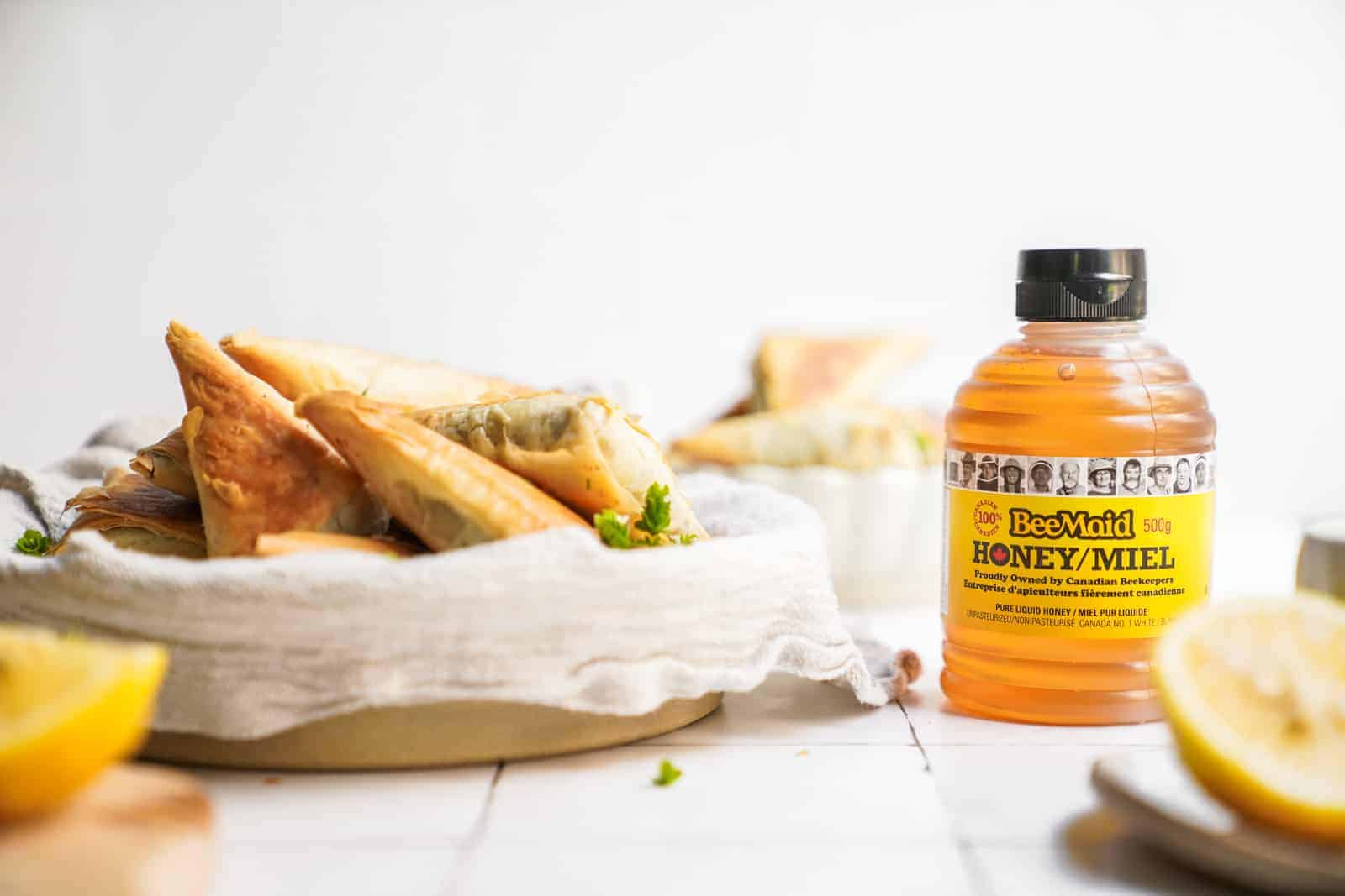 Bottle of honey on countertop surrounded by ingredients and mushroom pastry bites.