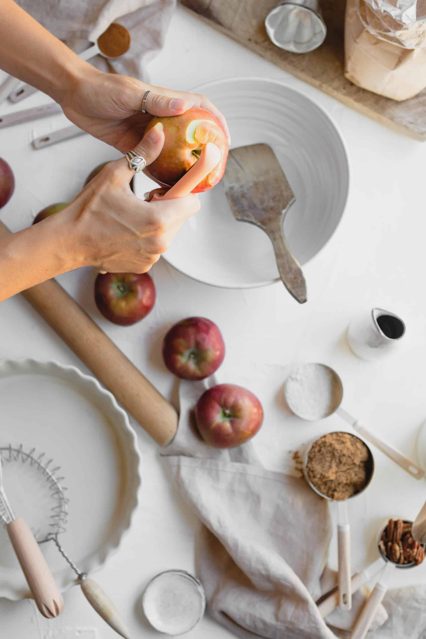 Hand peeling apple to make Vegan Apple Crumble.