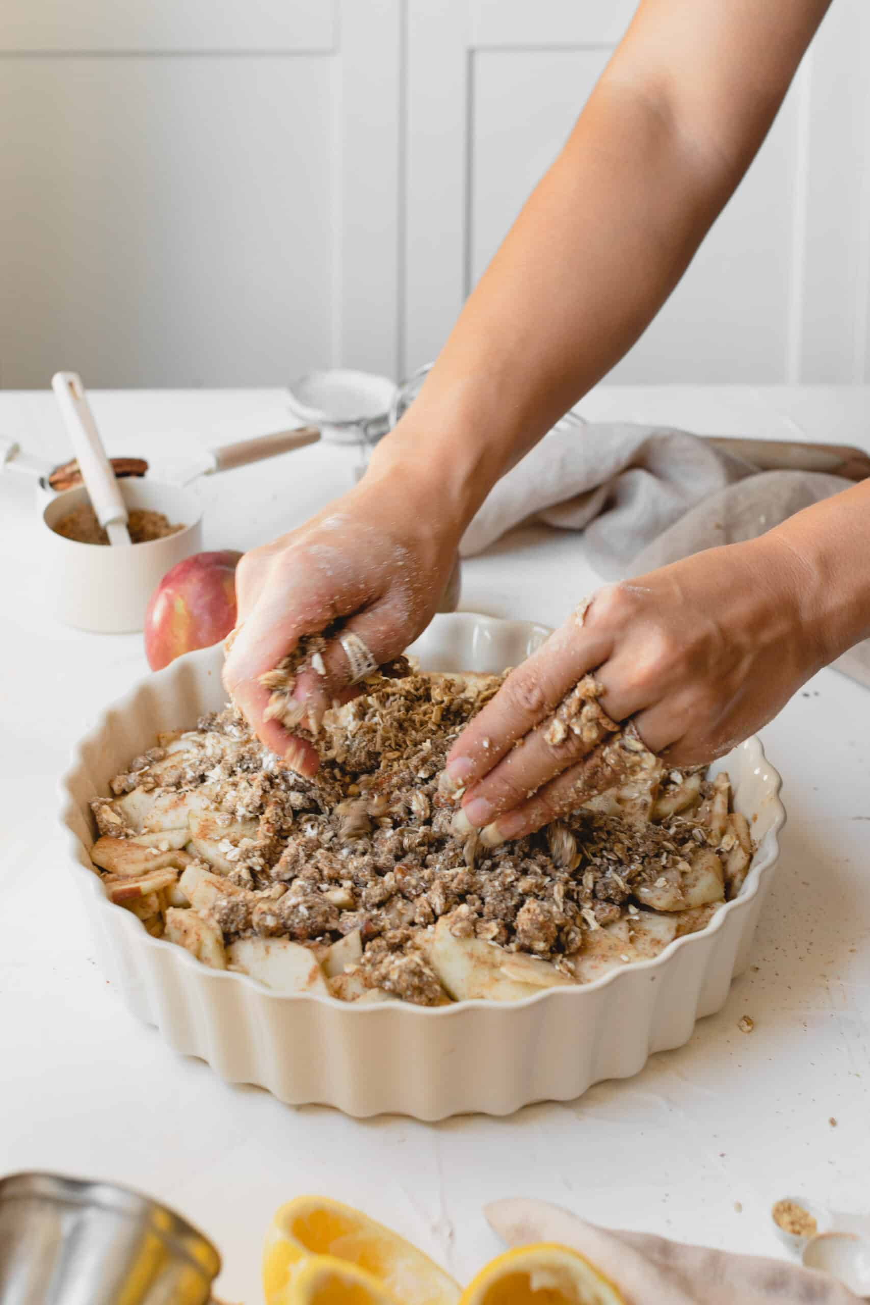 Person sprinkling the crumble on top of the apple in a serving dish.