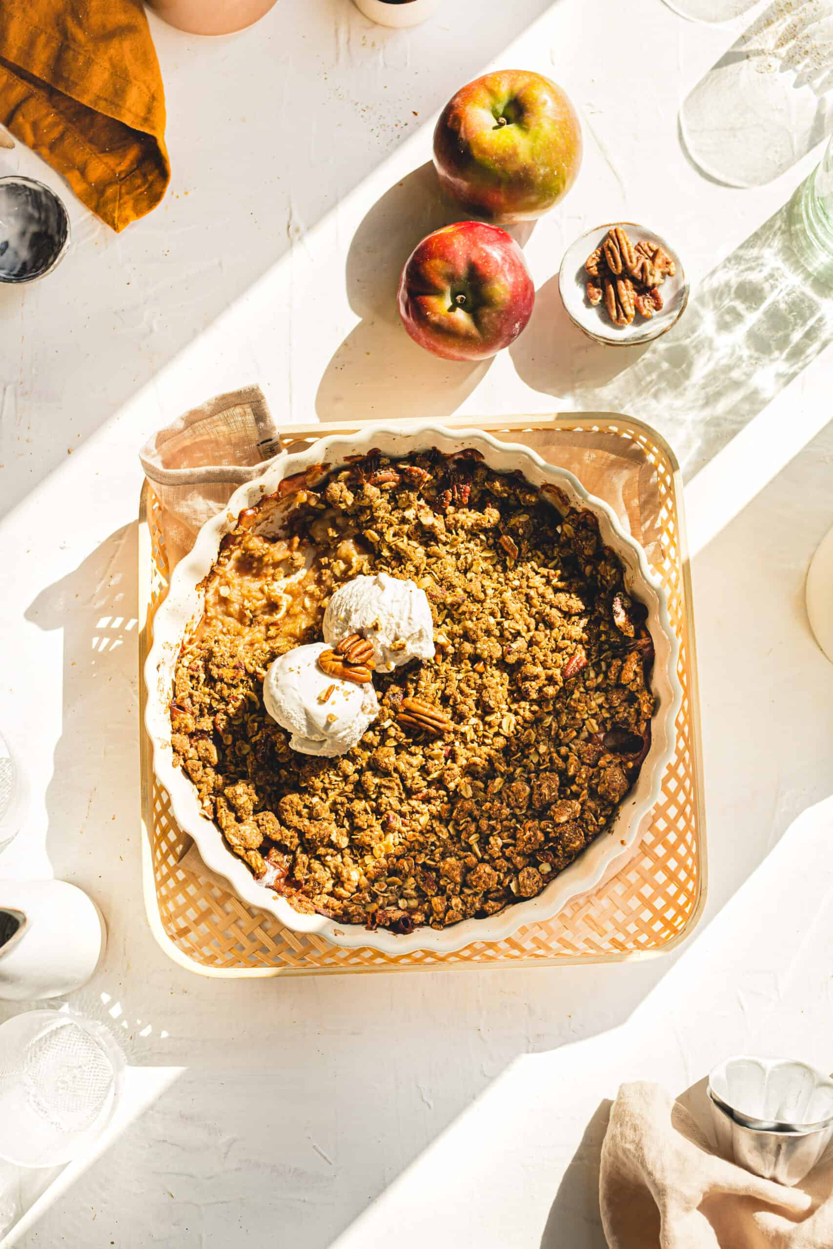 Vegan Apple Crumble with perfect sunlight shining in onto the serving dish with vanilla ice cream.