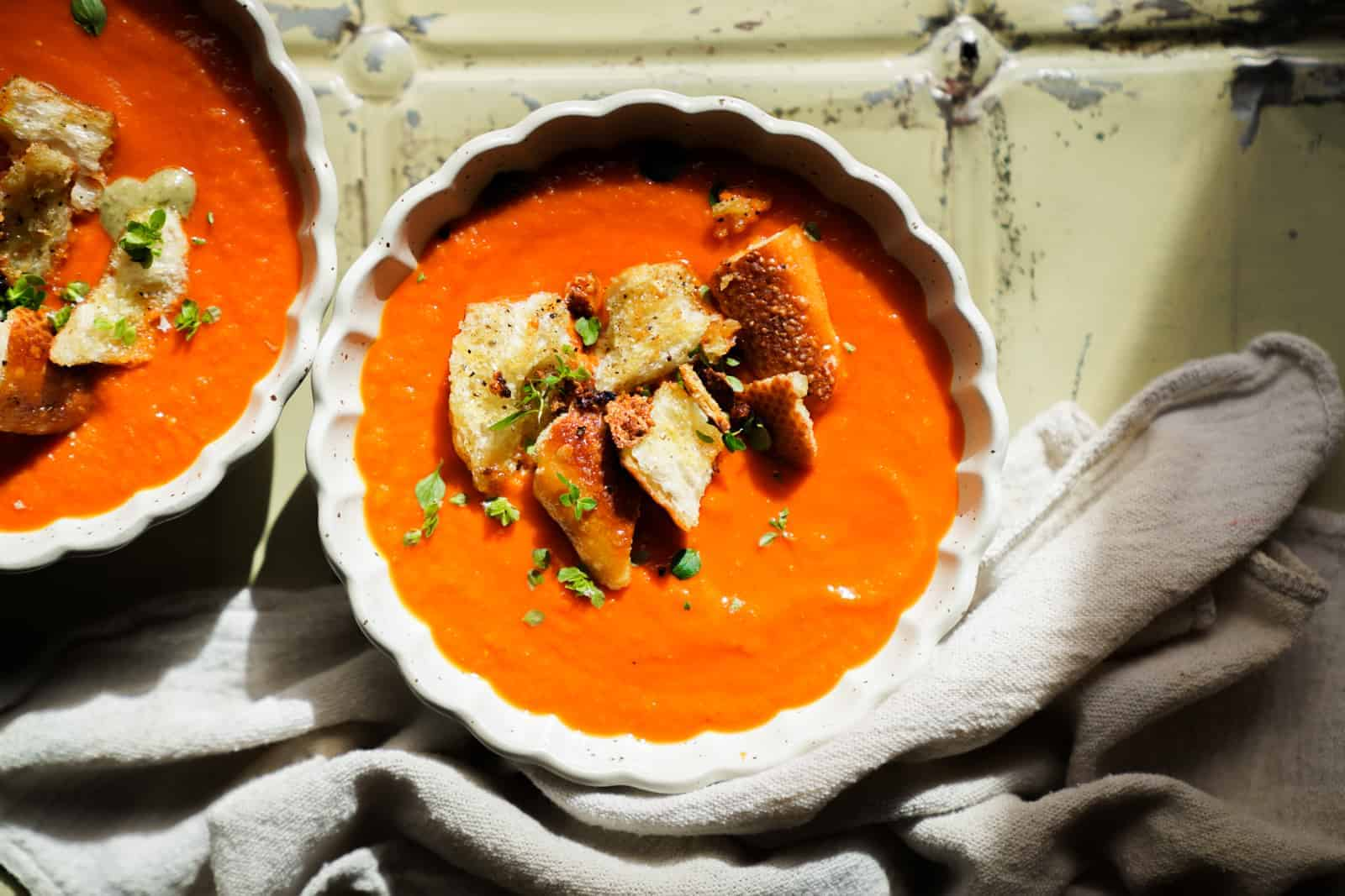 Overhead photo of Roasted Tomato Soup with garlic crotons and basil on top