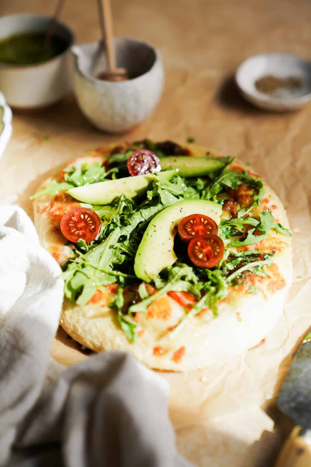 A well lit Vegetarian Breakfast Pizza with gorgeous green toppings