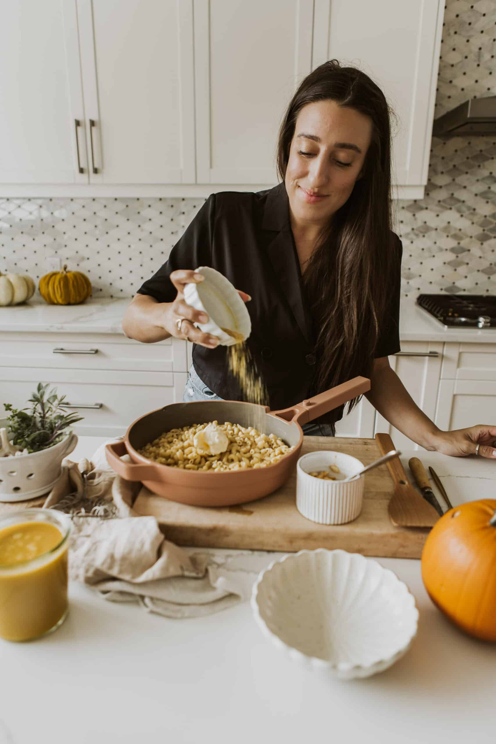 Maria pouring toppings on Vegan Pumpkin Mac and Cheese
