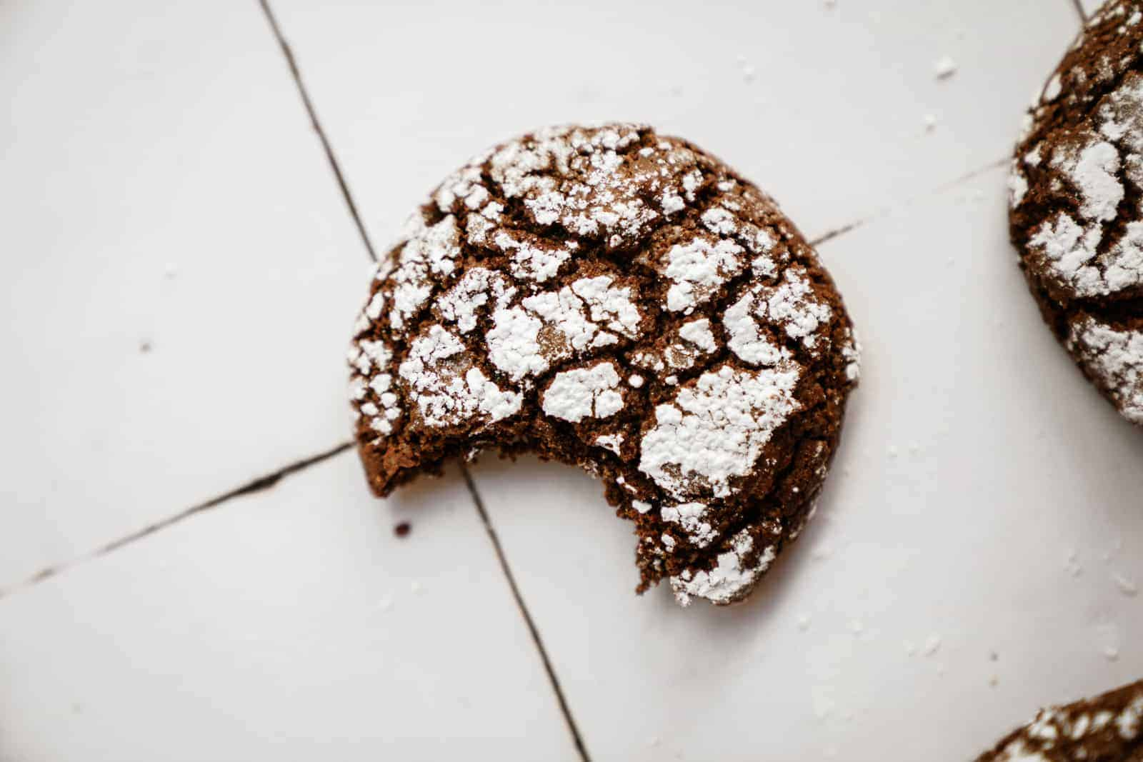 This Chocolate Crinkle Cookie Recipe is to die for. Cookie on white counter with bite out of it.