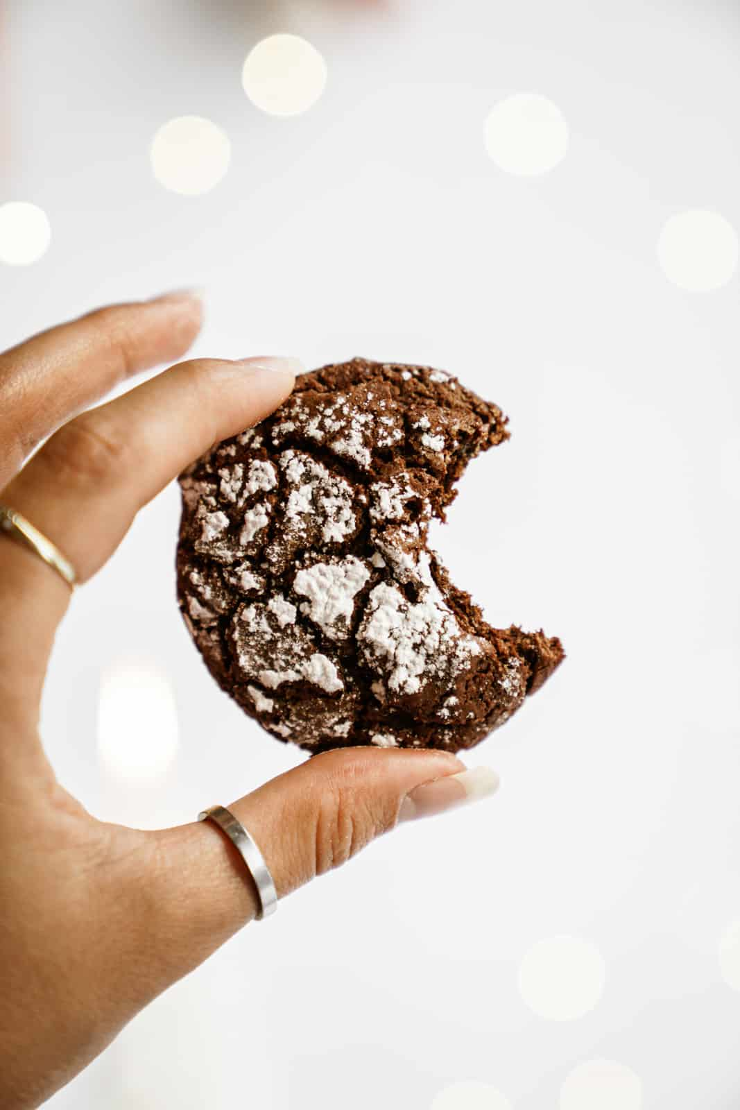 Hand holding a cookie from my Chocolate Crinkle Cookie Recipe with a bite out of it.