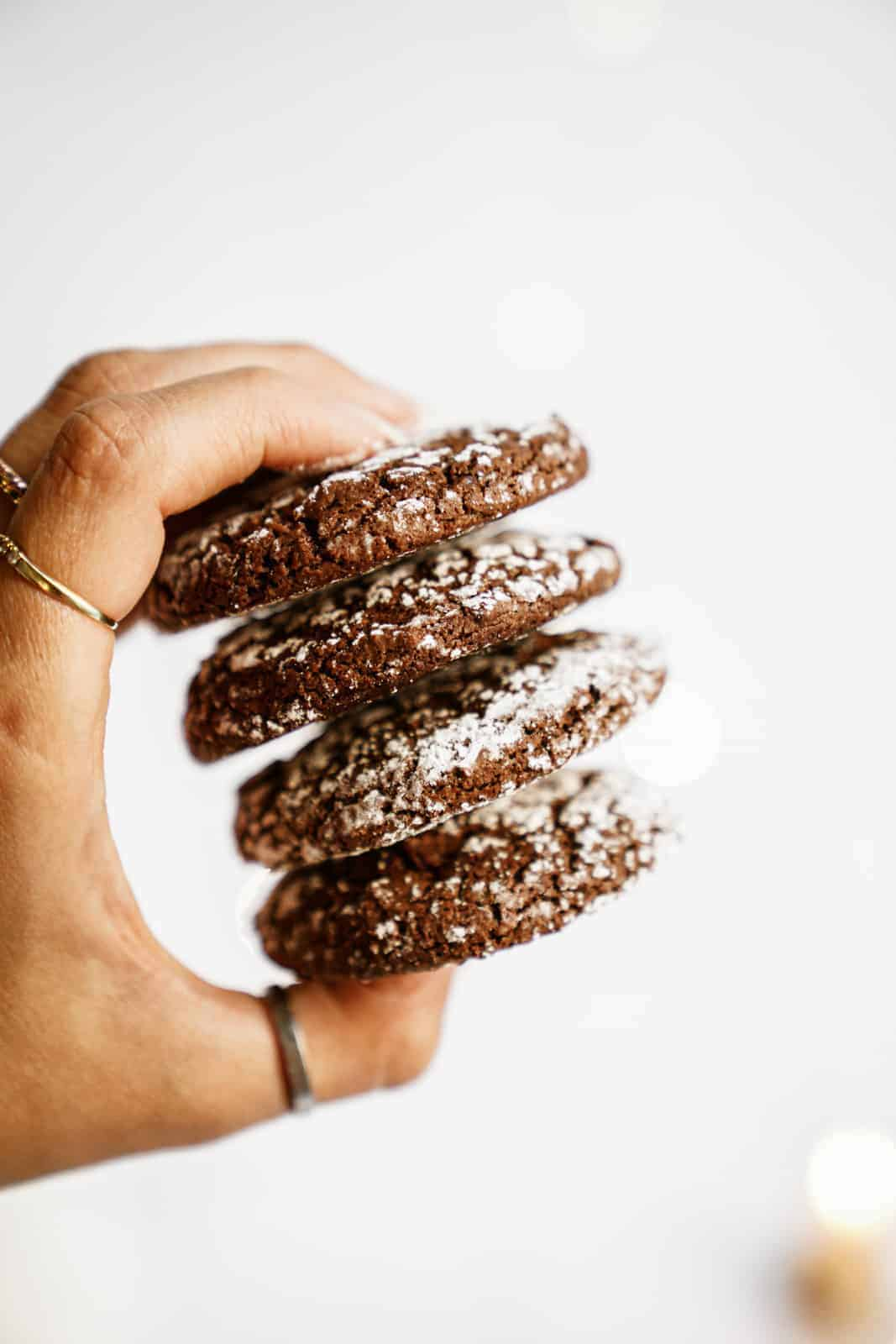 Hand holding a stack of the Chocolate Crinkle Cookie Recipe cookies.