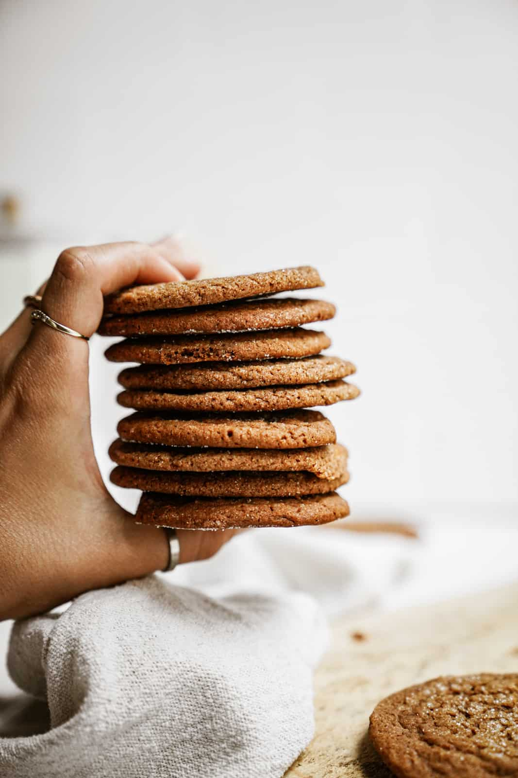 Hand holding a stack of Vegan Ginger Snap Cookies
