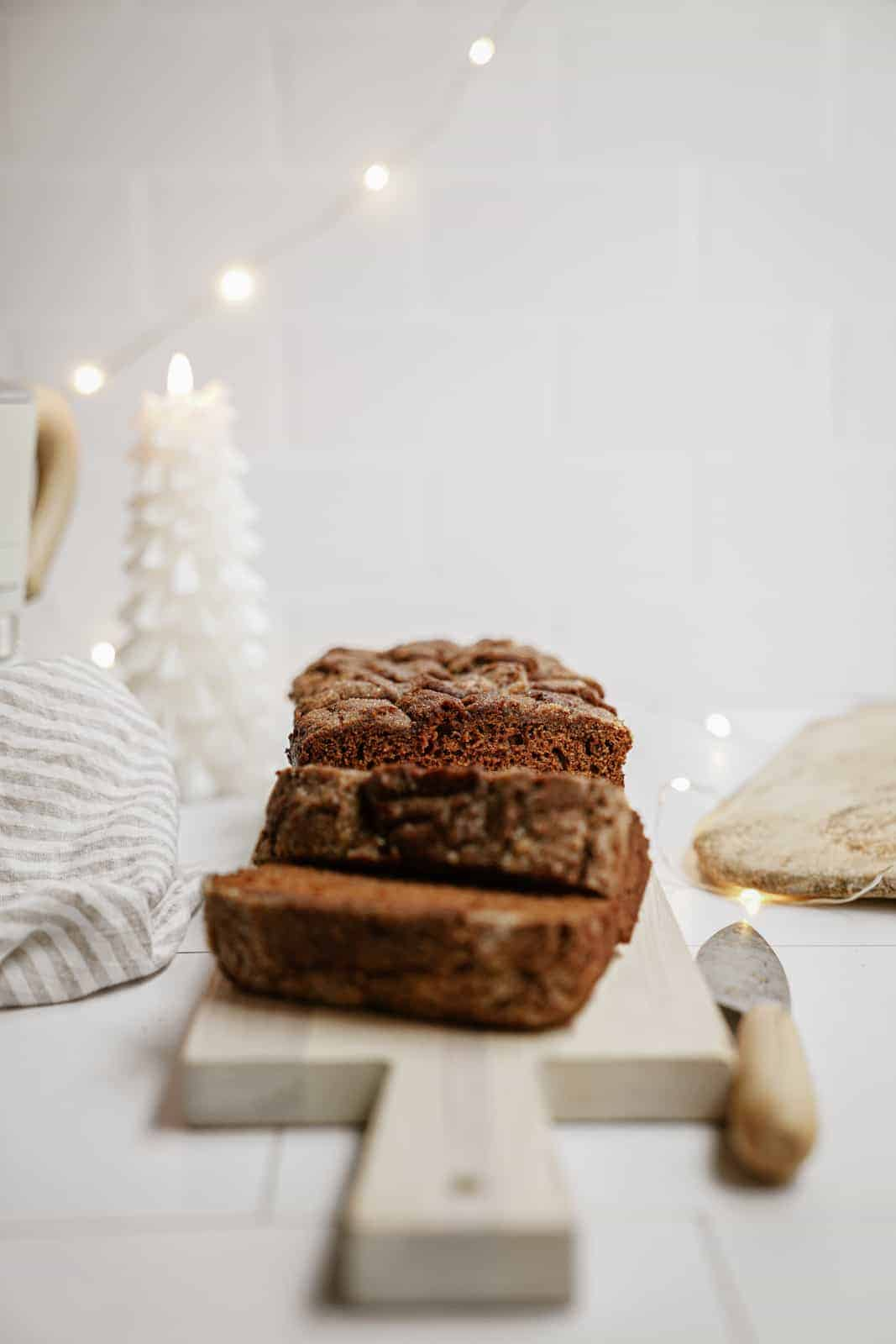 Vegan gingerbread loaf sliced on cutting board.