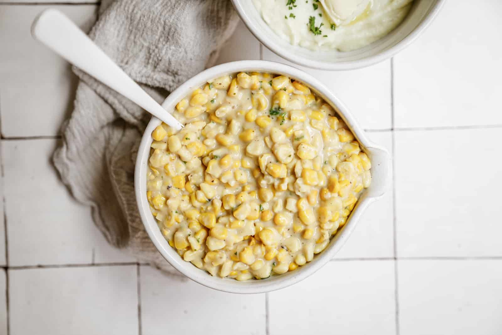 Creamed corn recipe in a serving dish on a white countertop.