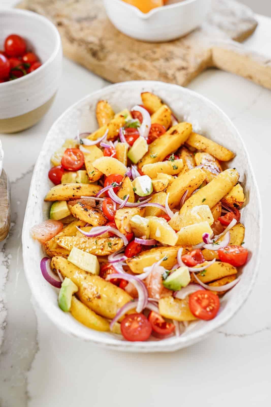 Big serving dish of vegan roasted potato salad with fresh veggies and citrus flavor.