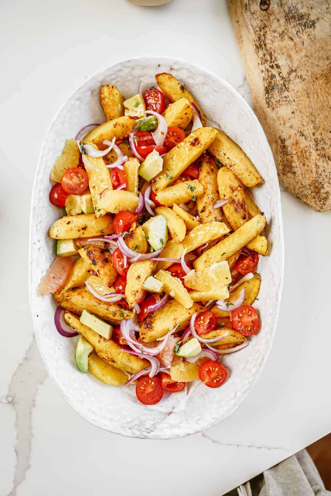 Serving dish filled with colorful vegan roasted potato salad.