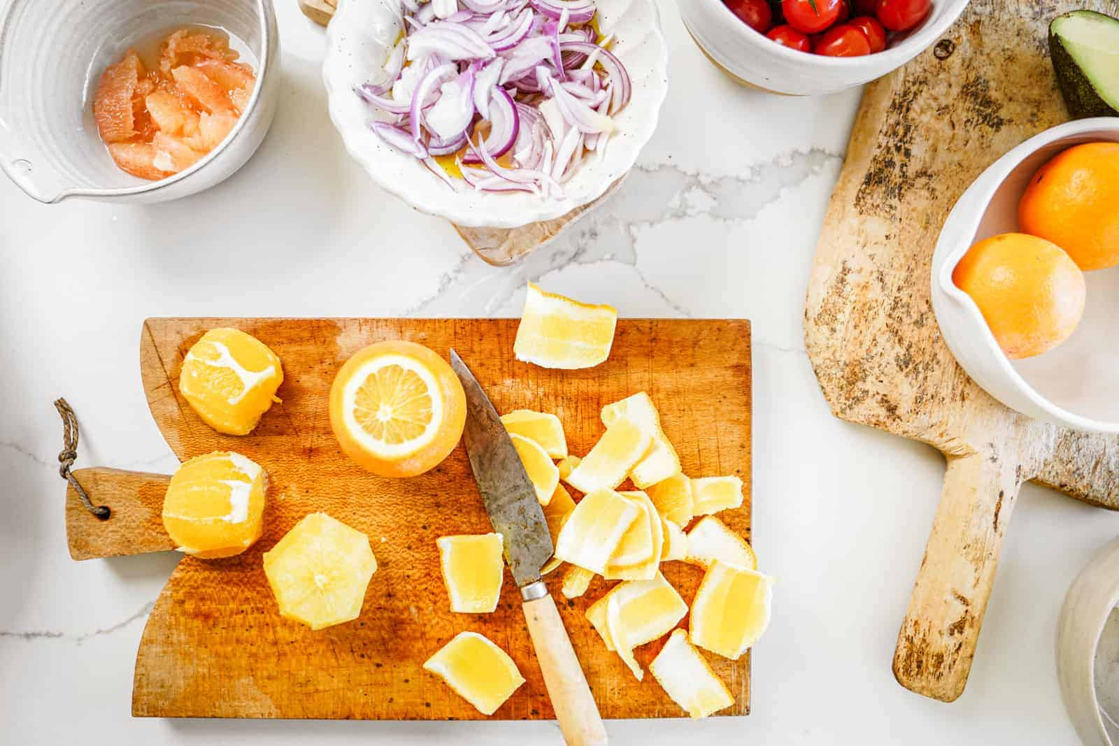 Cutting board of oranges being cut, surrounded by bowls of ingredients for roasted potato salad.