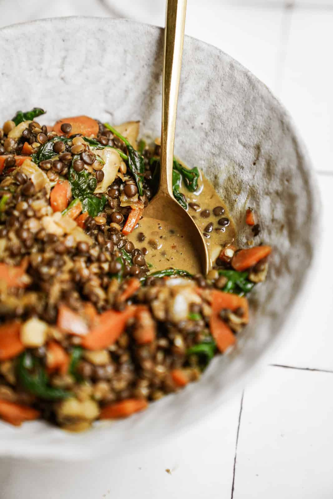 Lentils with Spinach in serving dish with spoon in the bowl.