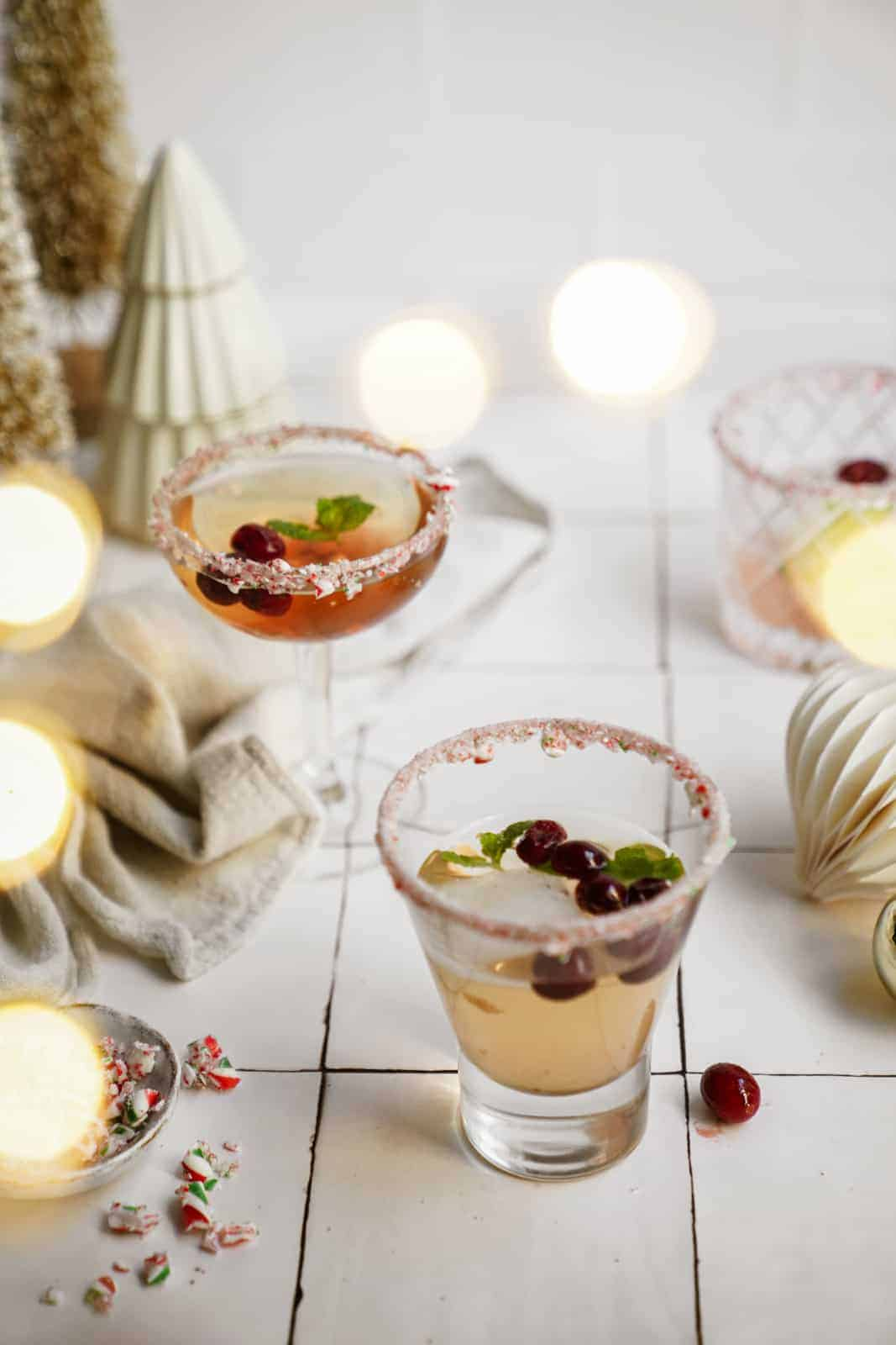 Candy cane martini in glasses on counter with a winter setting.