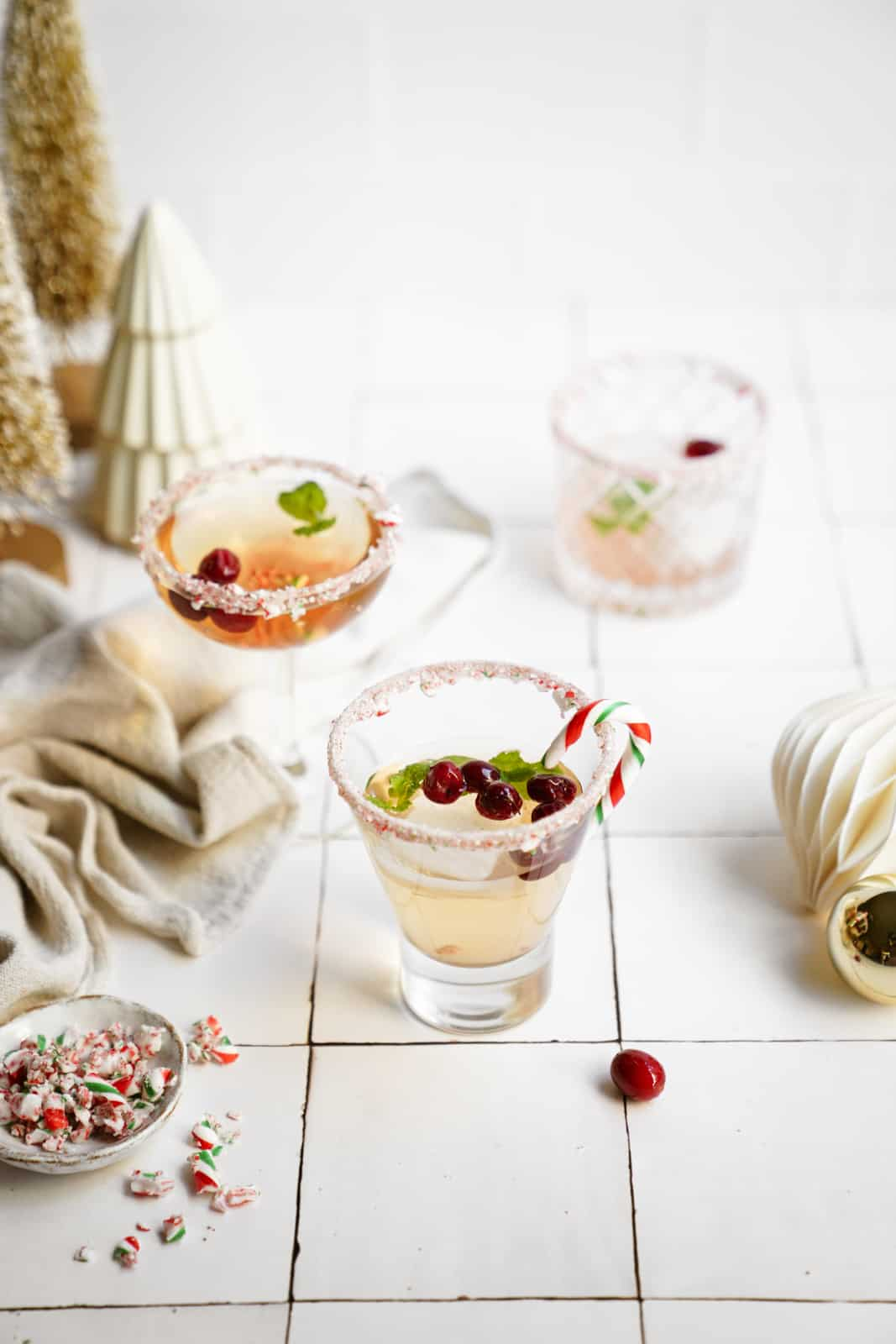 Candy Cane Martinis on countertop surrounded by holiday decor.