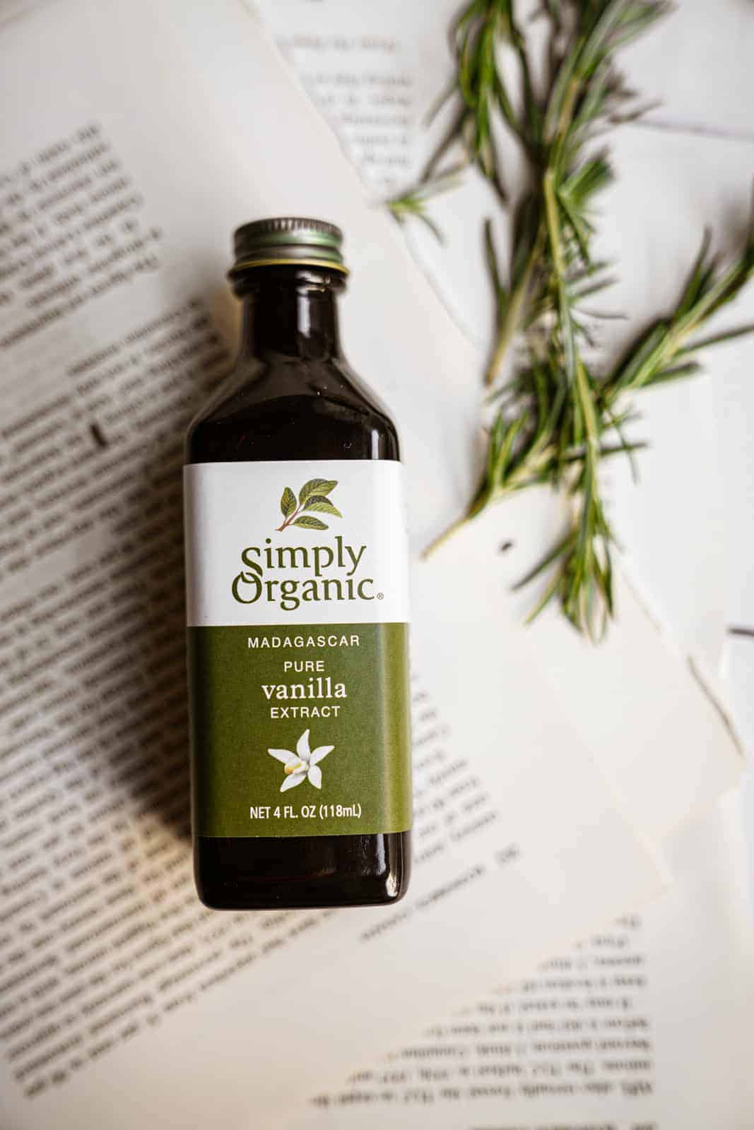 Simply Organics Pure Vanilla Extract laying on top of recipe with rosemary sprigs.