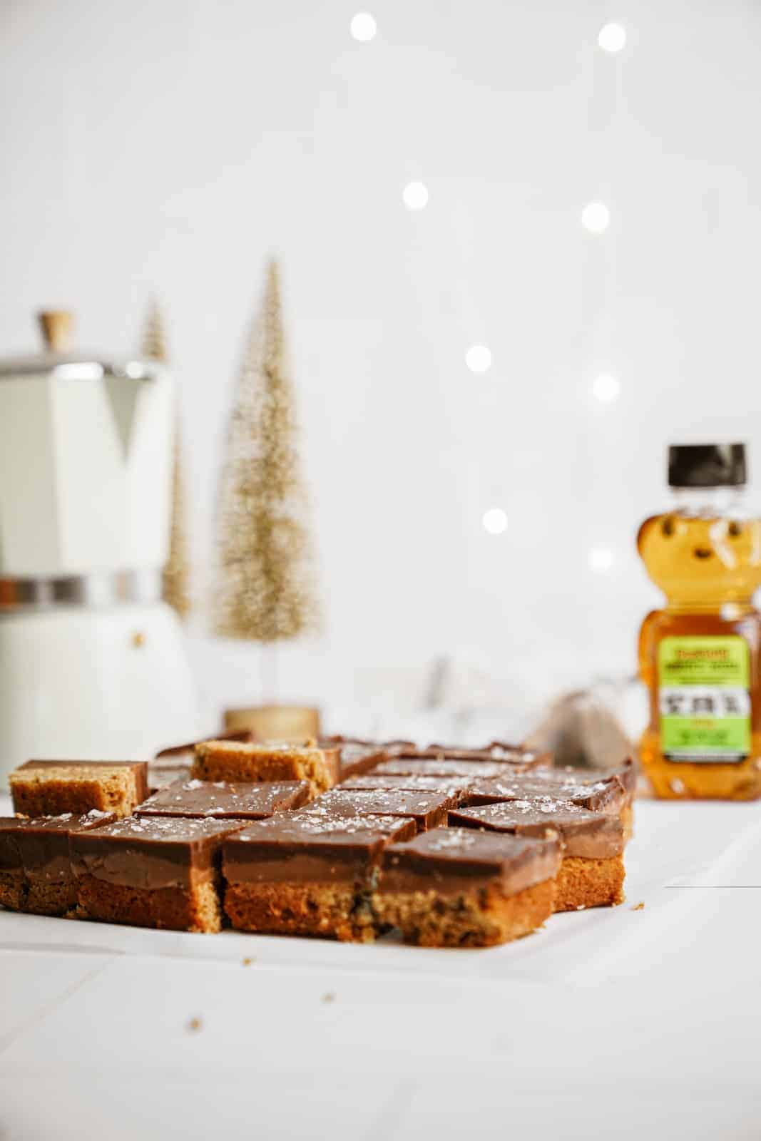 Caramel pretzel bars on a countertop with holiday backdrop, next to a BeeMaid honey container.