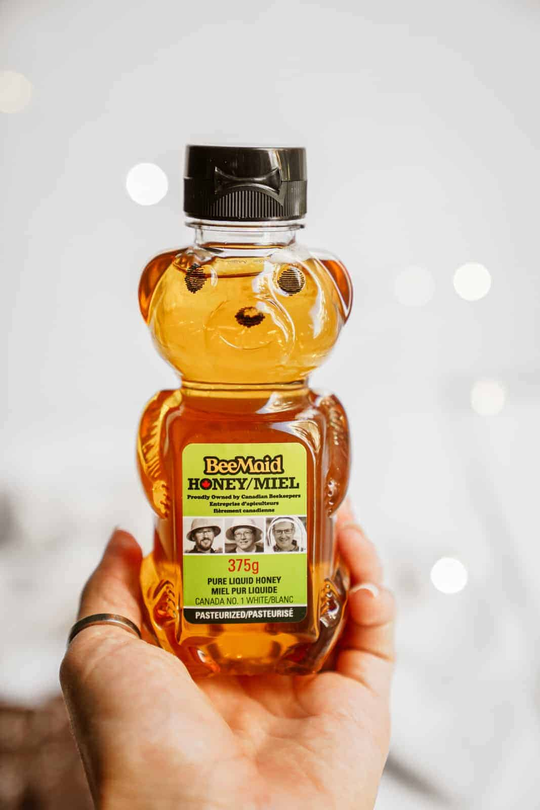 Hand holding a Beemaid honey container.