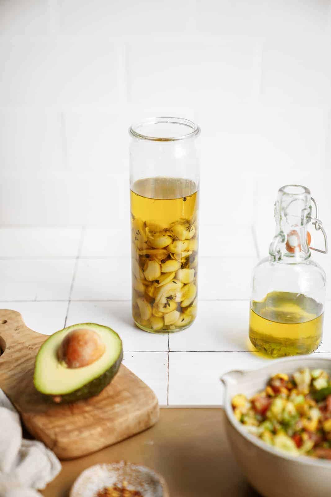 Jar of garlic confit next to a fresh salad and avocado.
