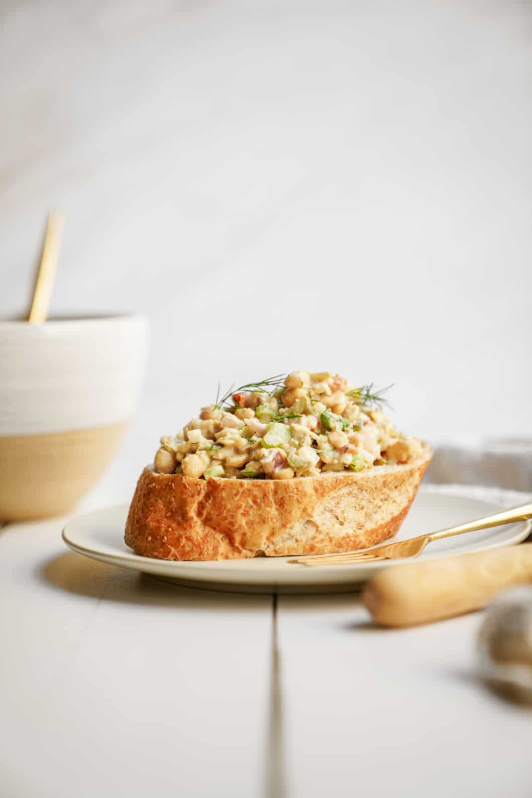 Mashed Chickpea Salad sitting on a piece of bread on a plate