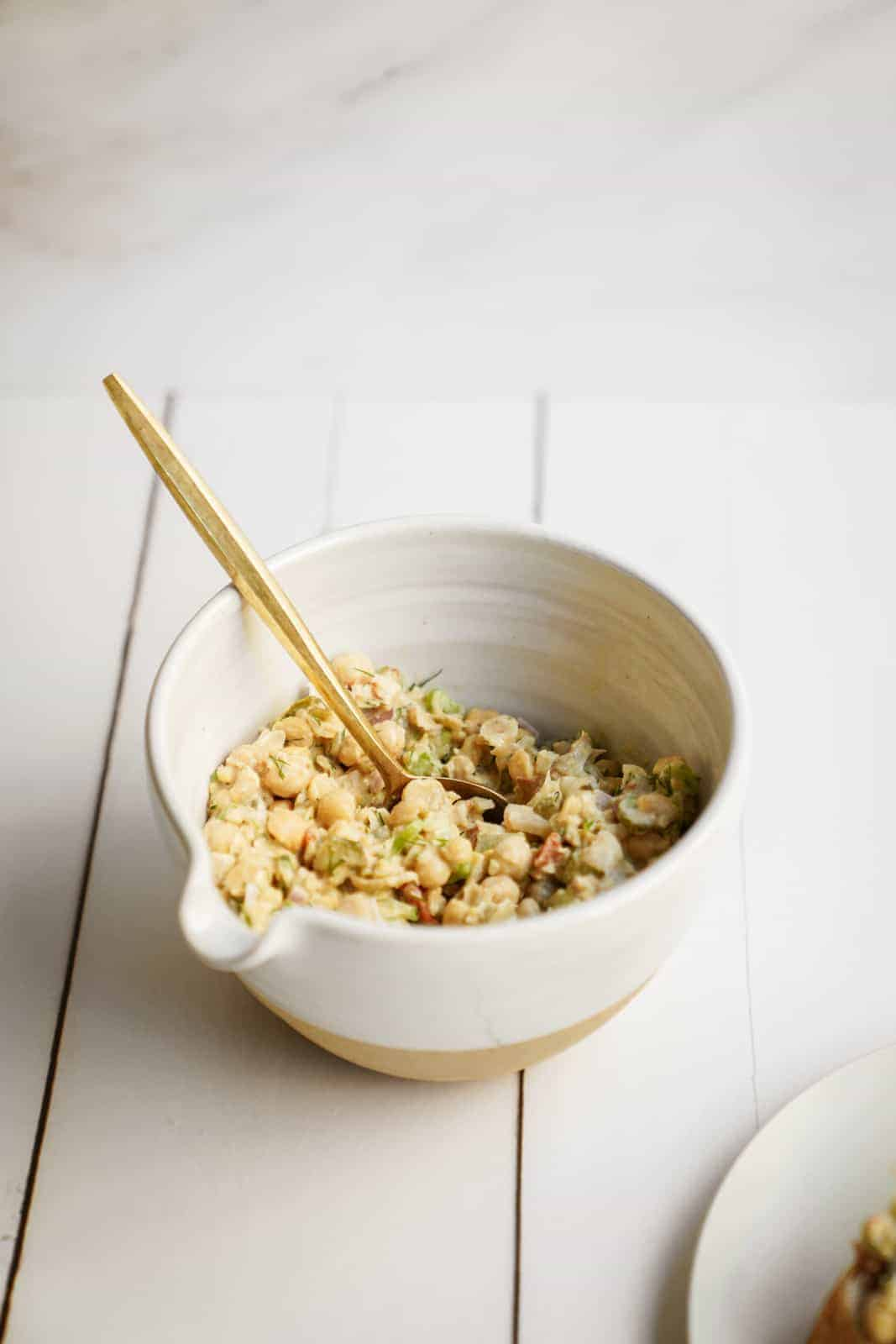 A big bowl of Mashed Chickpea Salad with a serving spoon