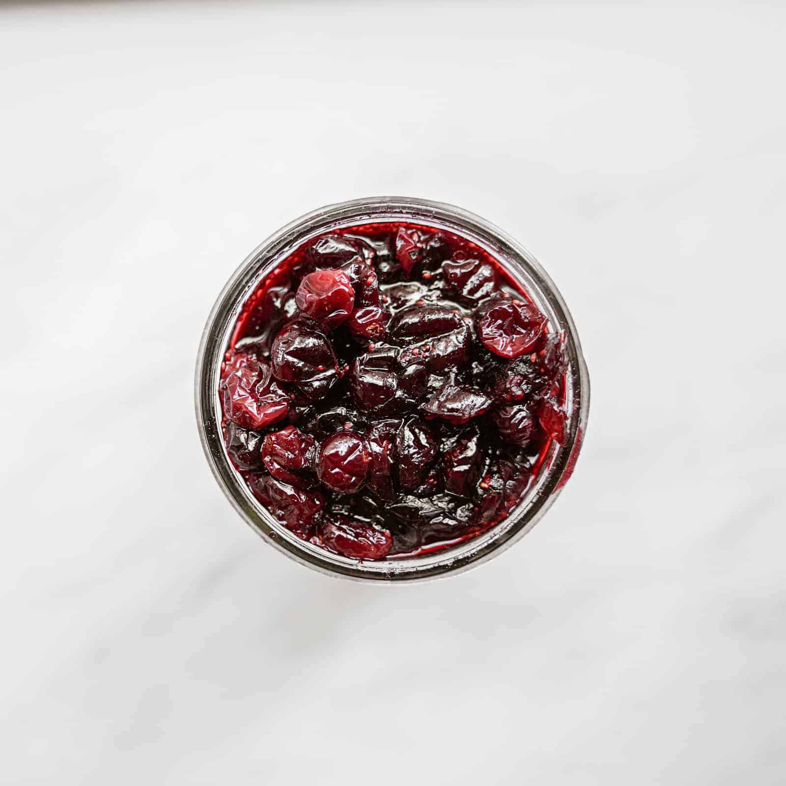 Top view of jar on counter with vegan cranberry sauce in it