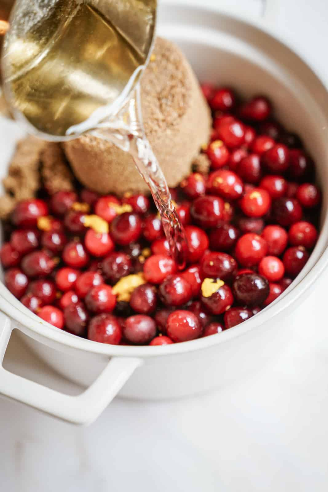 Water being added to fresh cranberries and sugar for vegan cranberry sauce