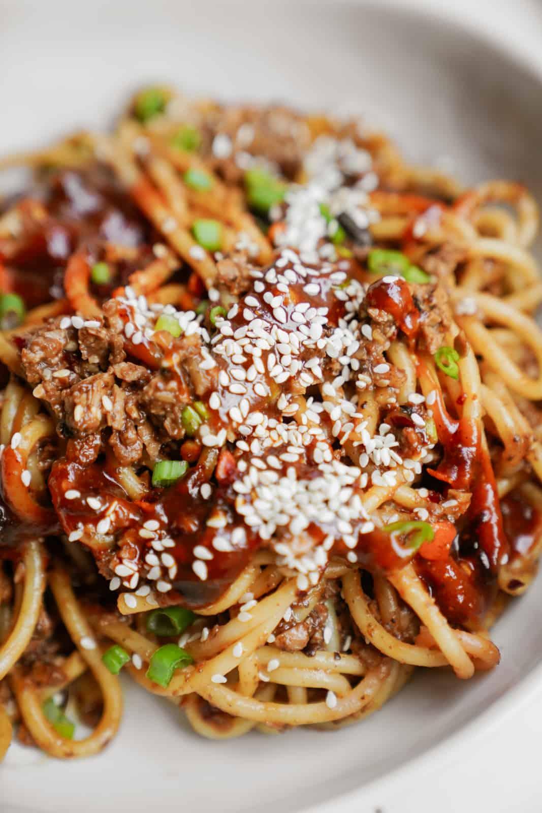 Closeup of vegan dan dan noodles in a white bowl