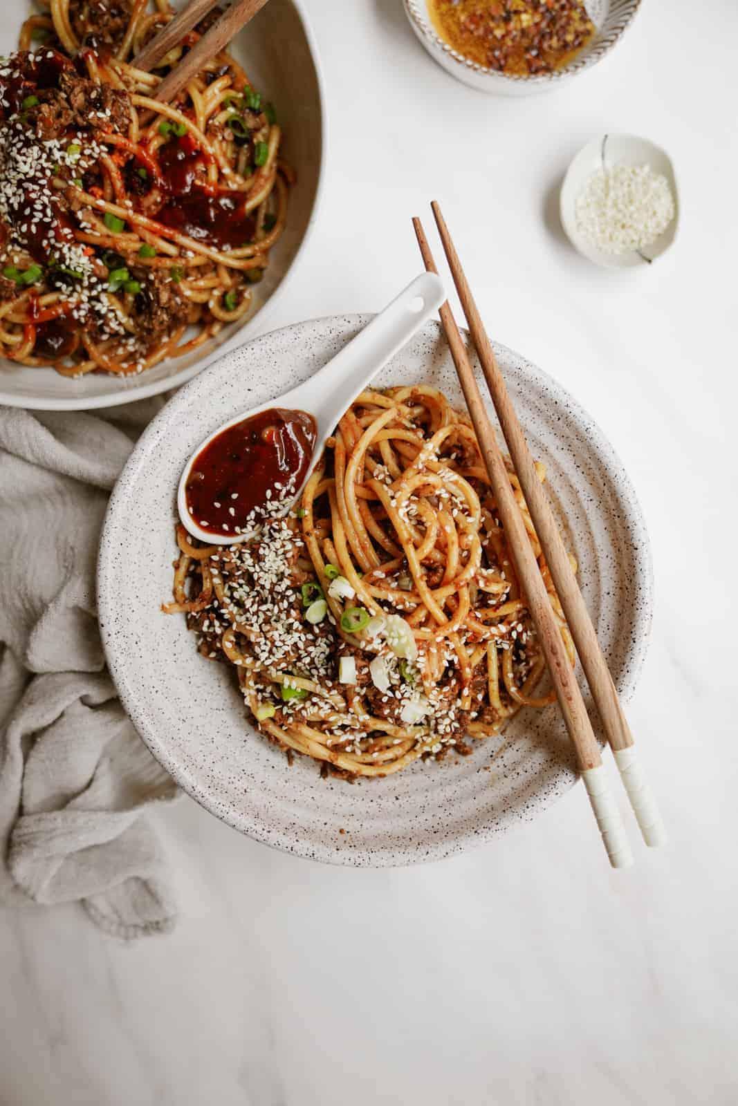 Vegan dan dan noodles in a white bowl with chopsticks.