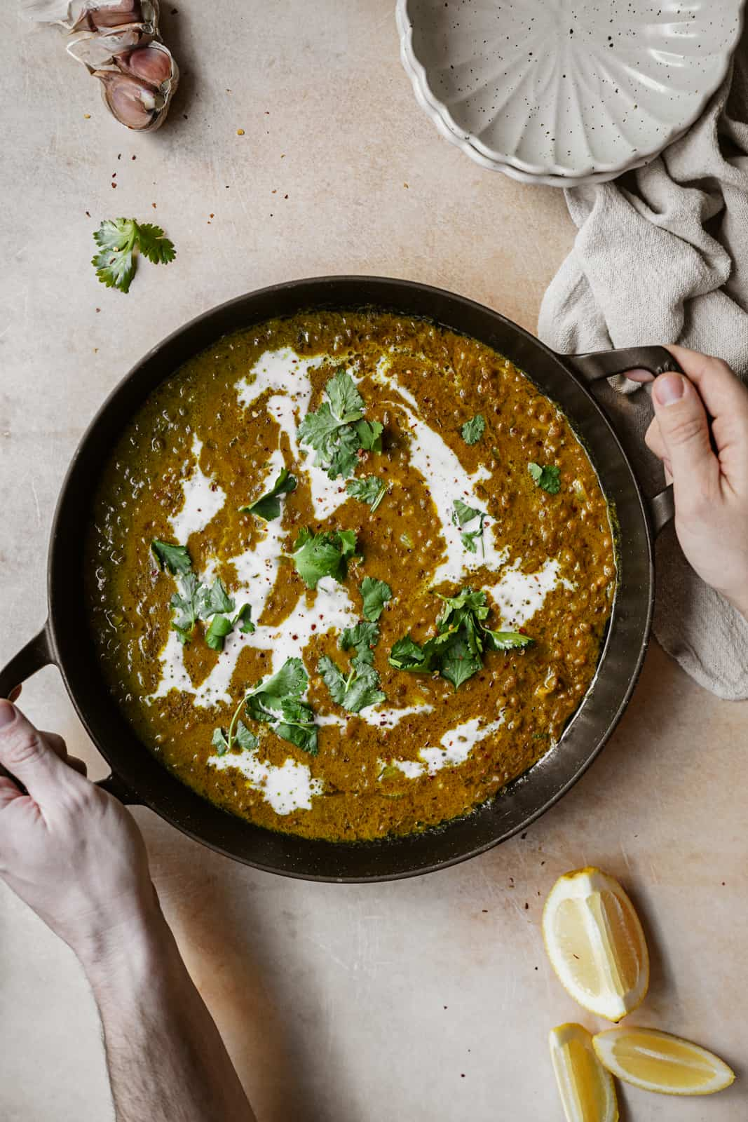 Green Lentil Curry in a serving dish with two hands holding it.
