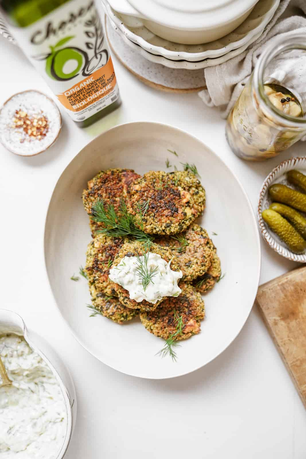 Quinoa and Spinach Patties on serving dish on countertop surrounded by ingredients.