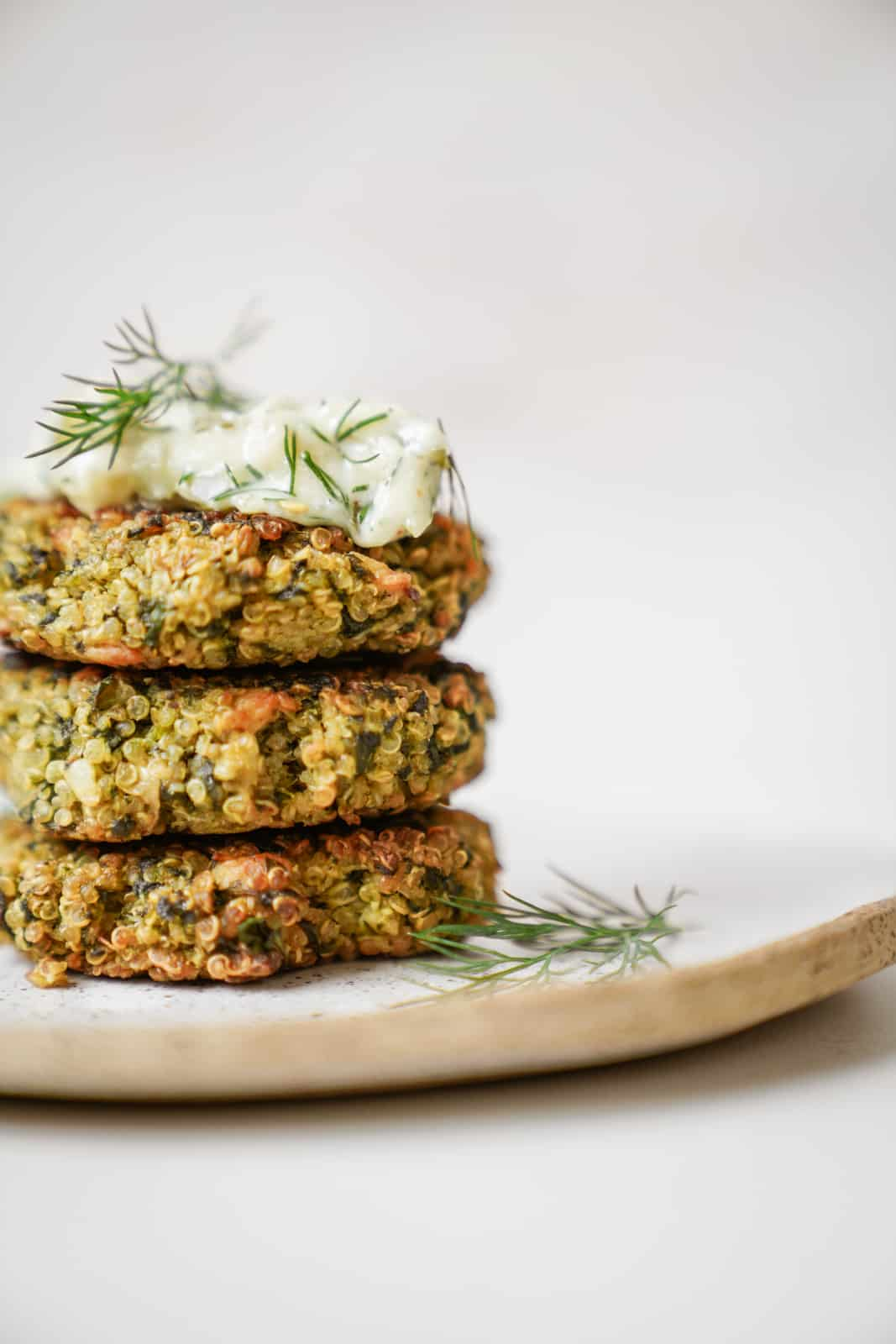 Close up of quinoa and spinach patties in serving dish topped with aioli.