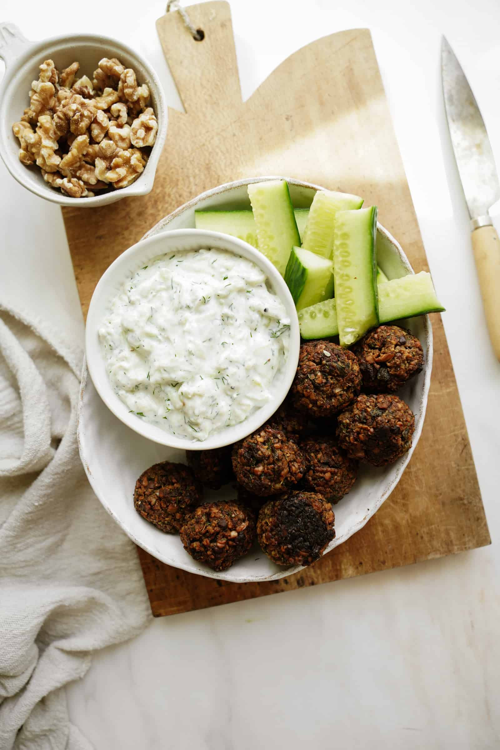 Greek Tzatziki recipe on a plate with fresh cucumber and falafel