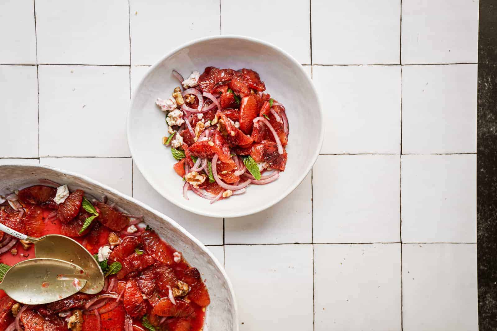Colorful blood orange salad in a bowl next to a large salad bowl on white countertop