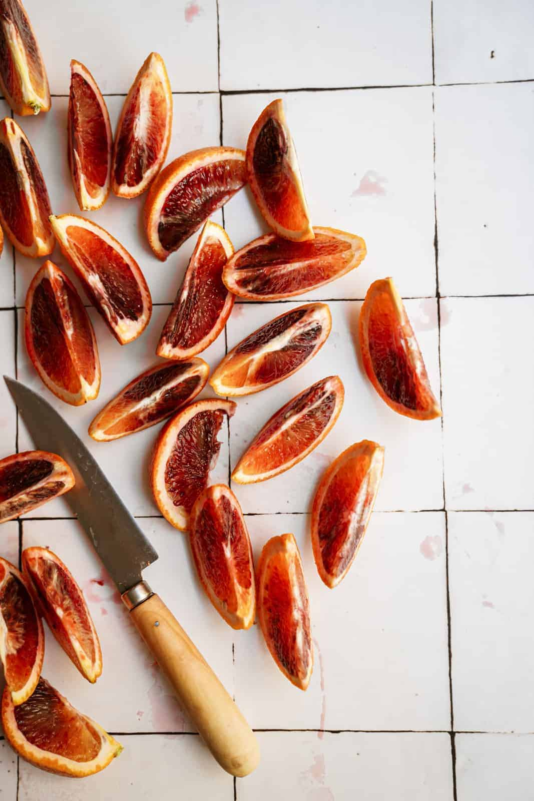 Slices of blood oranges on a white countertop for blood orange salad