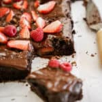 Chocolate Vegan Sheet Cake recipe on countertop cut into squares.