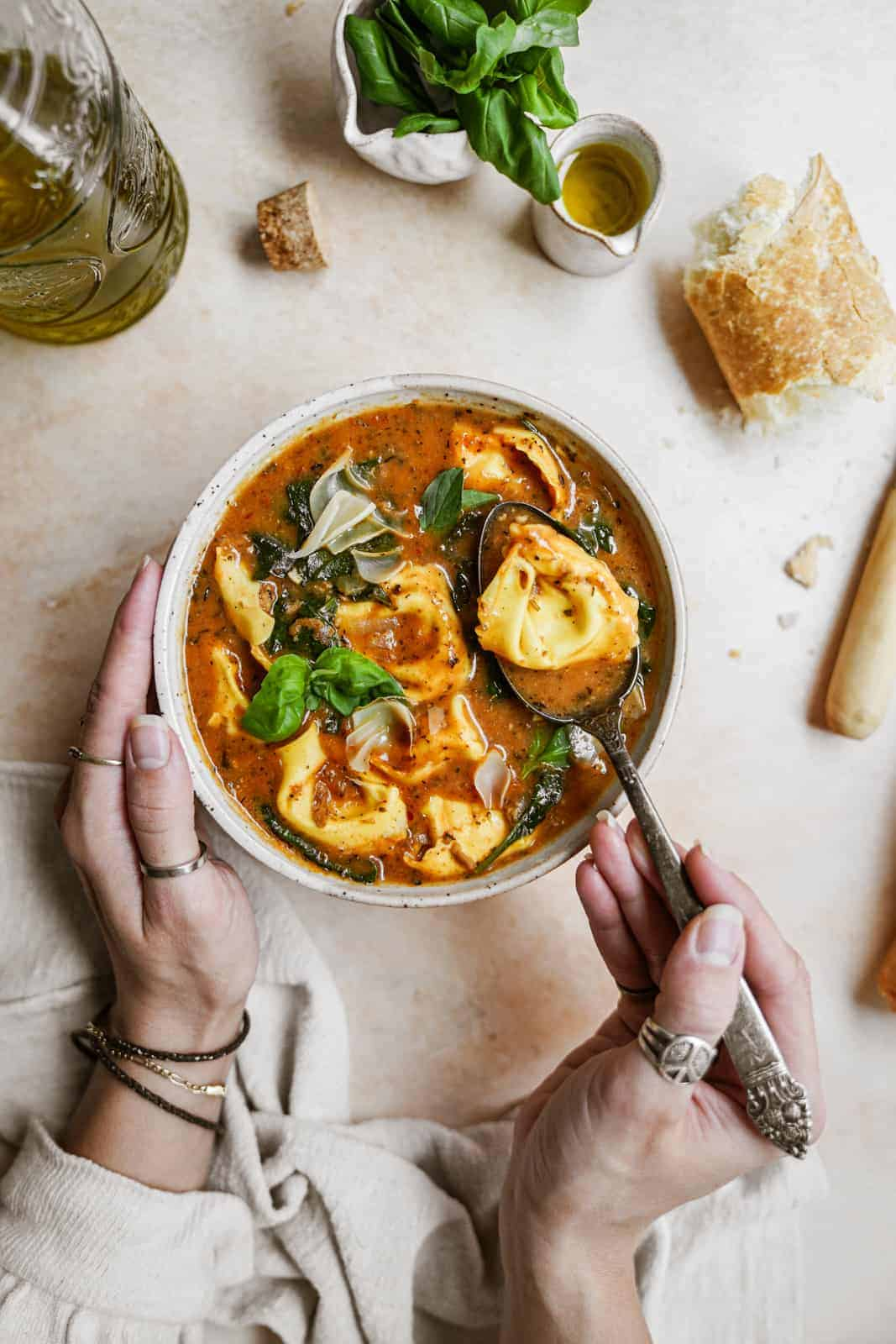 Hands holding bowl of vegan tortellini soup on countertop