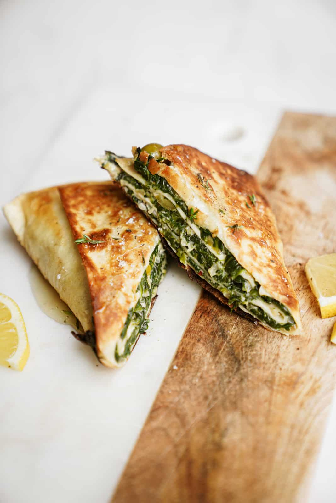 Trendy spinach wrap made greek-style cut into triangles on countertop.